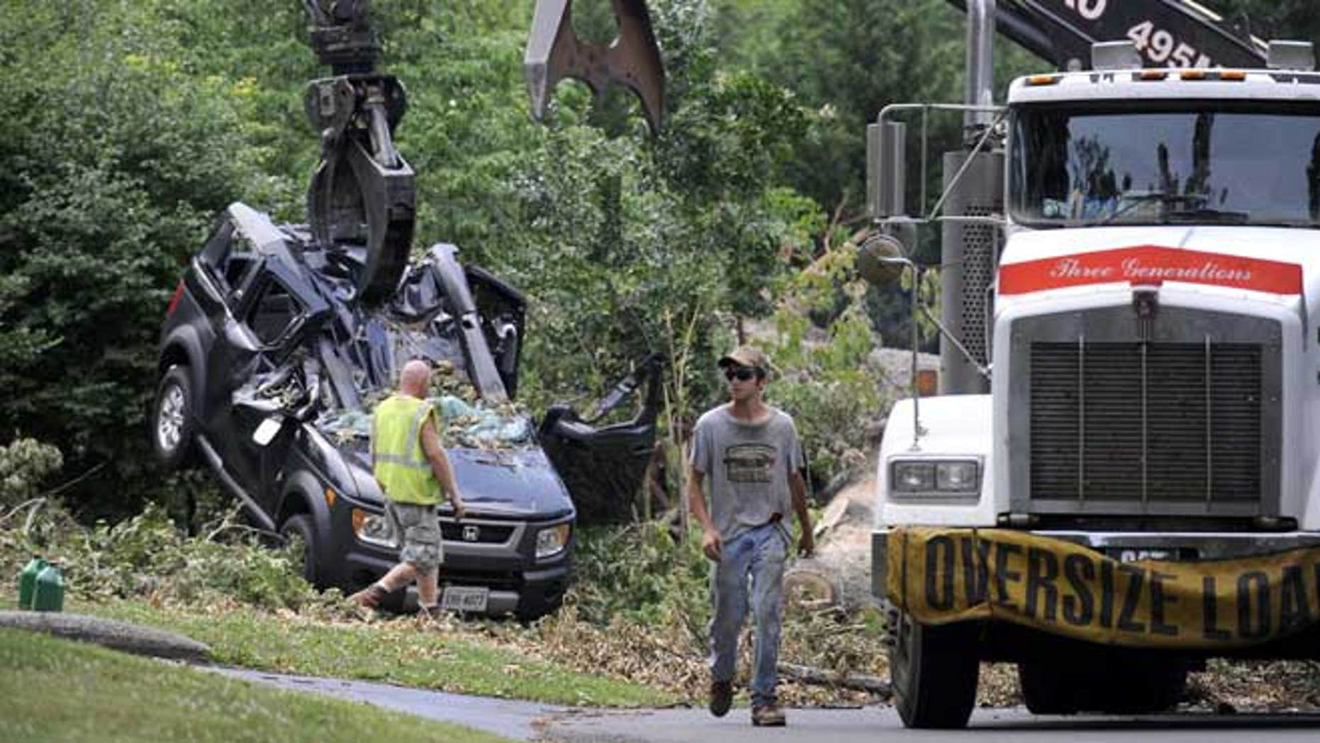 July 4, 2012: In the process of cutting up and removing an Oak tree blocking Inglewood Road, in Lynchburg, Va., a crane lifts the crushed Honda Element that Amy Scott and her son, Cooper, were inside of Friday night as the tree fell on top of them.