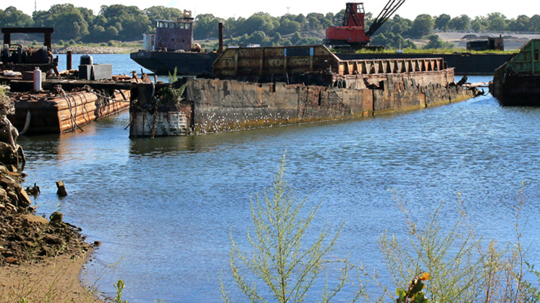 In this Monday, Aug. 22, 2016, photo, rusting remnants of an old Russian submarine that once was used as a floating museum until it sank in 2007, remains in the Providence river in Providence, R.I. The state wants it gone.