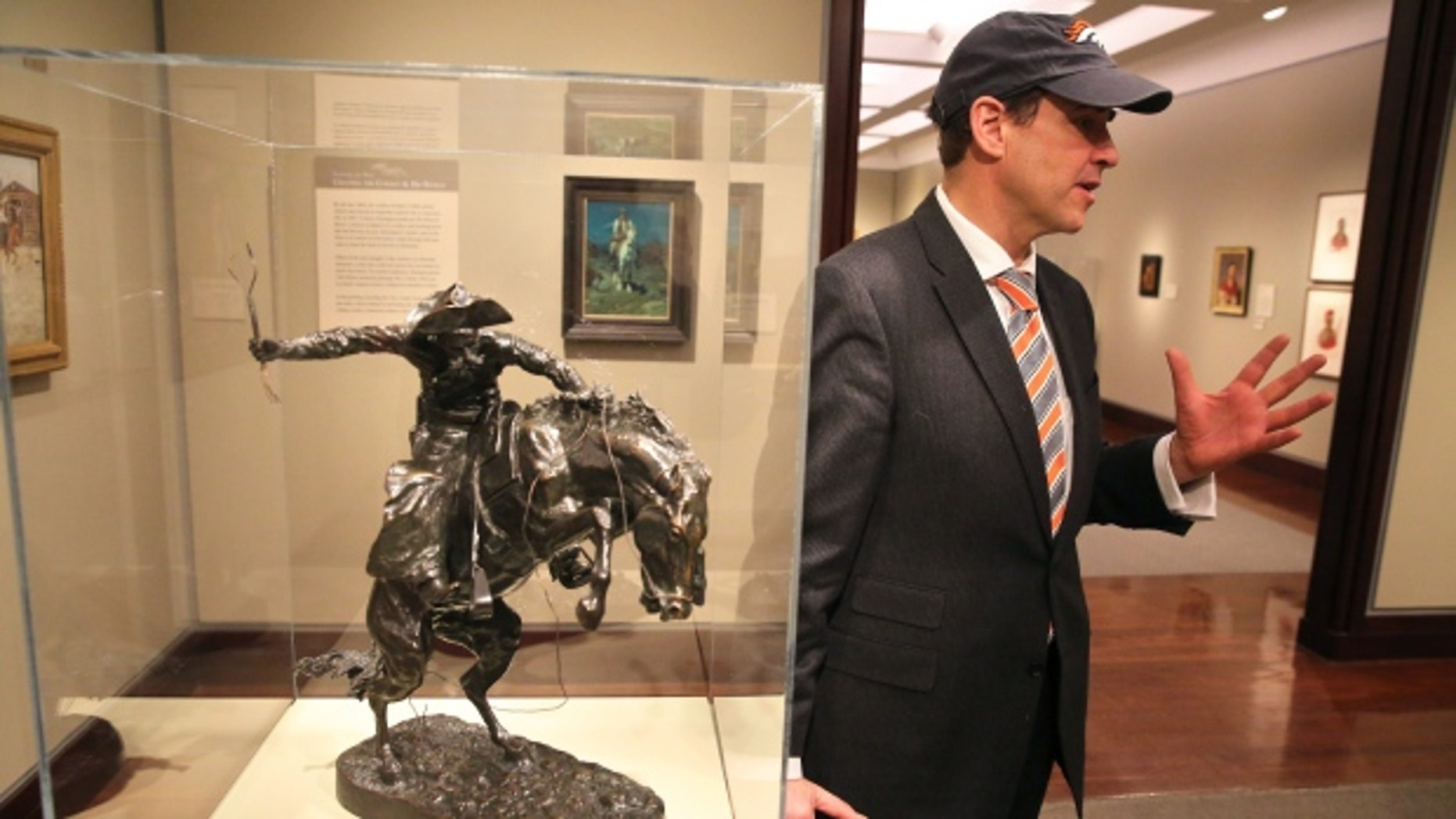 January 29, 2014: Denver Art Museum director Christoph Heinrich poses next to a Frederic Remington bronze of a cowboy riding a bucking horse, part of the museum's collection. The Denver and Seattle Art Museums have started a friendly wager: if the Broncos win the Super Bowl against the Seahawks, Seattle will send a Seahawk mask to Denver for three months. If the Seahawks win, Denver sends the Remington statue to Seattle for three months. (Brennan Linsley/Associated Press)