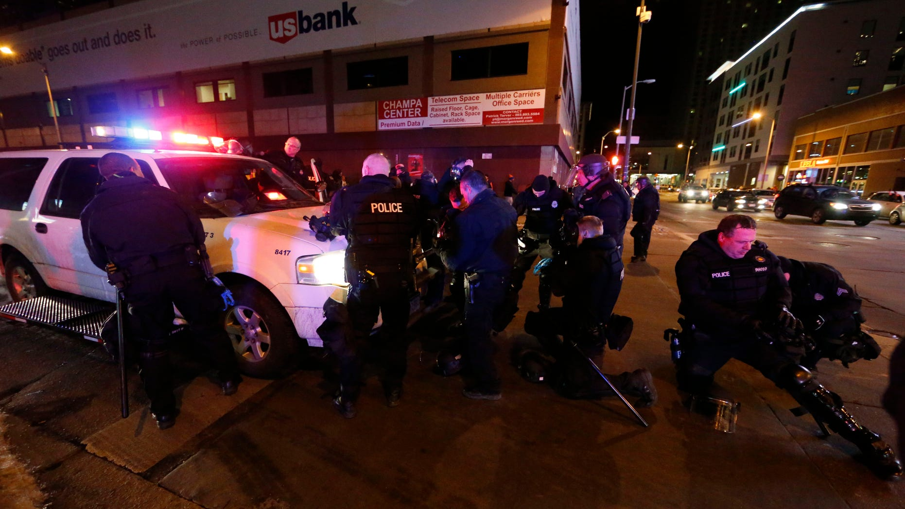 Denver police officers don gas masks and riot gear as they prepare to move back Broncos fans celebrating Denver's win in the Super Bowl.