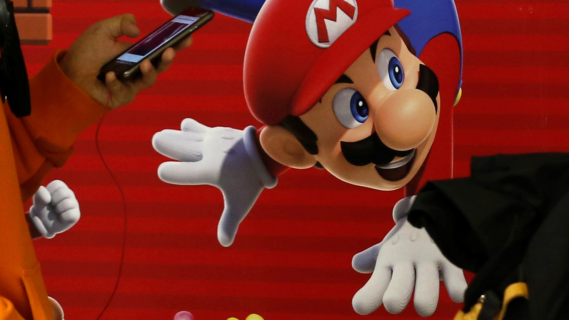 "A man using a smartphone walks past Nintendo's ""Super Mario Run"" game advertisement board at a subway station in Tokyo, Japan, December 21, 2016. REUTERS/Kim Kyung-Hoon - RC1AFC22EB90"