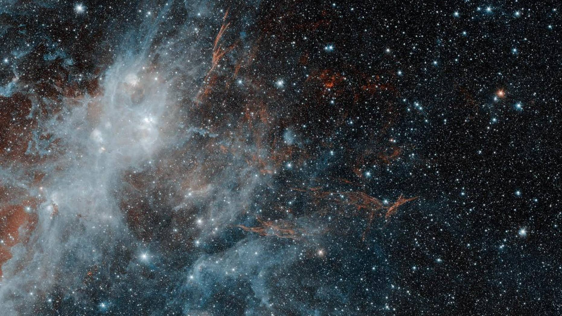 The supernova remnant HBH 3 glows with infrared light in this photo from NASA's Spitzer Space Telescope. Infrared light with a wavelength of 3.6 microns is shown in blue, while lower-energy infrared light with a wavelength of 4.5 microns is shown in red. Spitzer captured this image in May 2010, and NASA released it on Aug. 2, 2018.