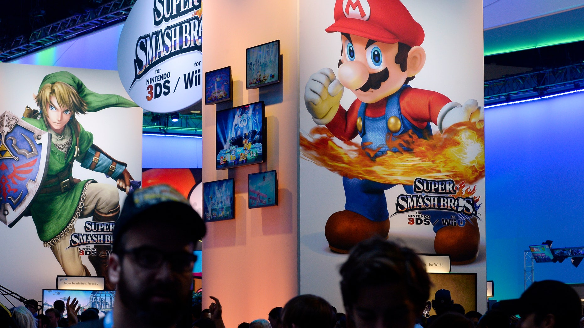 Attendees walk past Nintendo Co.'s Super Smash Bros. signage at the 2014 Electronic Entertainment Expo, known as E3, in Los Angeles, California June 11, 2014.