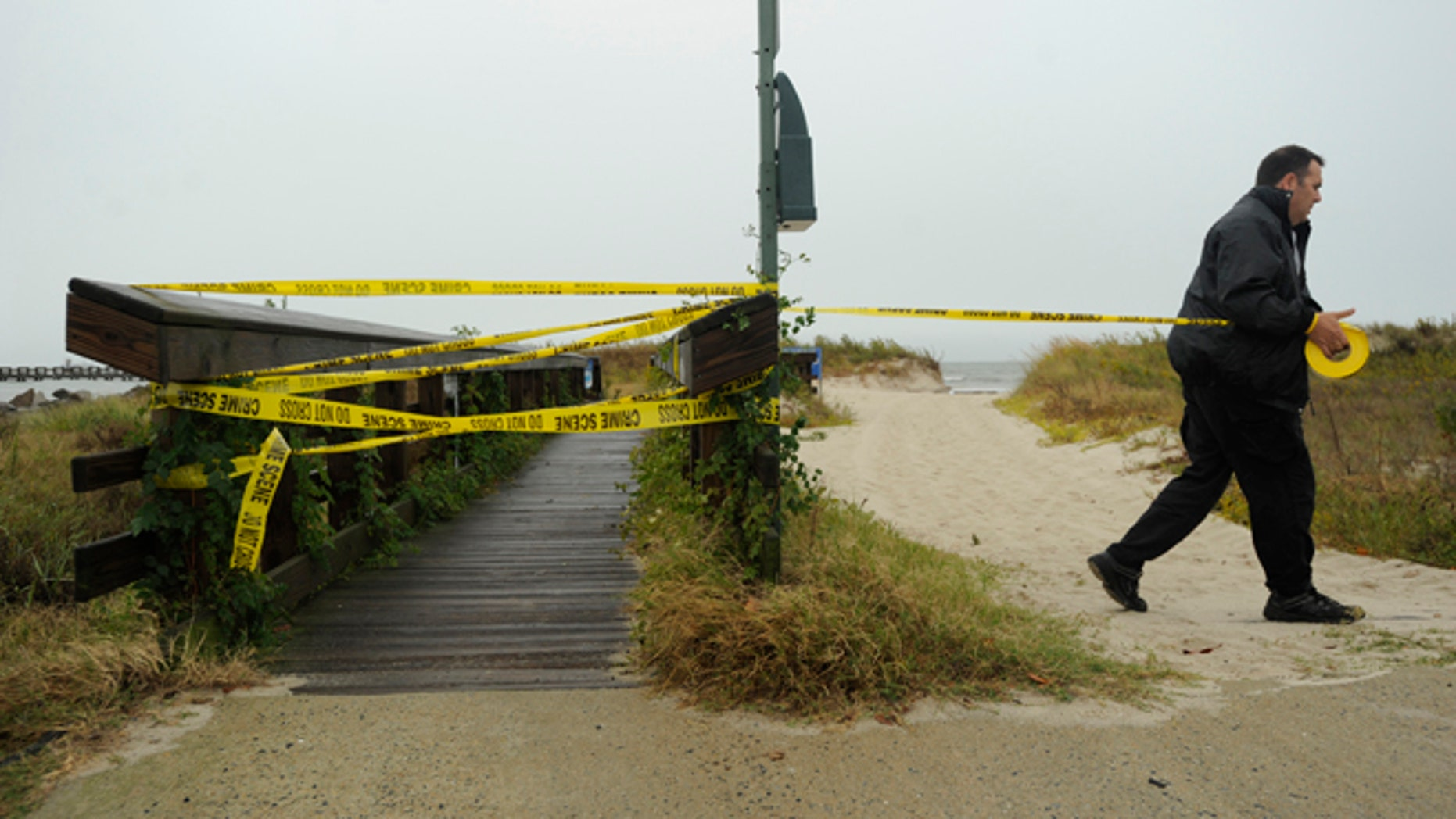 Oct. 28, 2012: Cape Charles Police Officer Jim Pruitt tapes off the town fishing pier and beach to restrict access in Cape Charles, Va., ahead of Hurricane Sandy.
