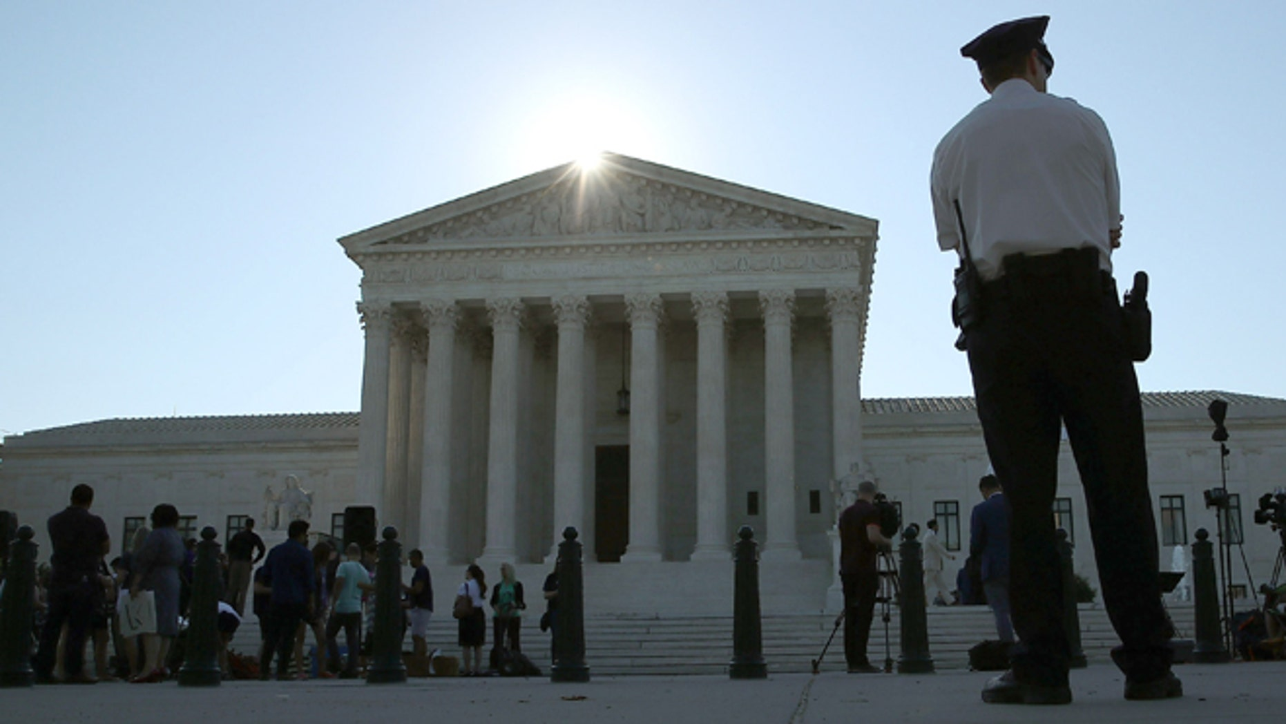 WASHINGTON, DC - JUNE 20: A police officer stands in front of the U.S. Supreme Court building June 20, 2016 in Washington, DC. The high court still has four decisions to hand down before their summer break next week.  (Photo by Mark Wilson/Getty Images)