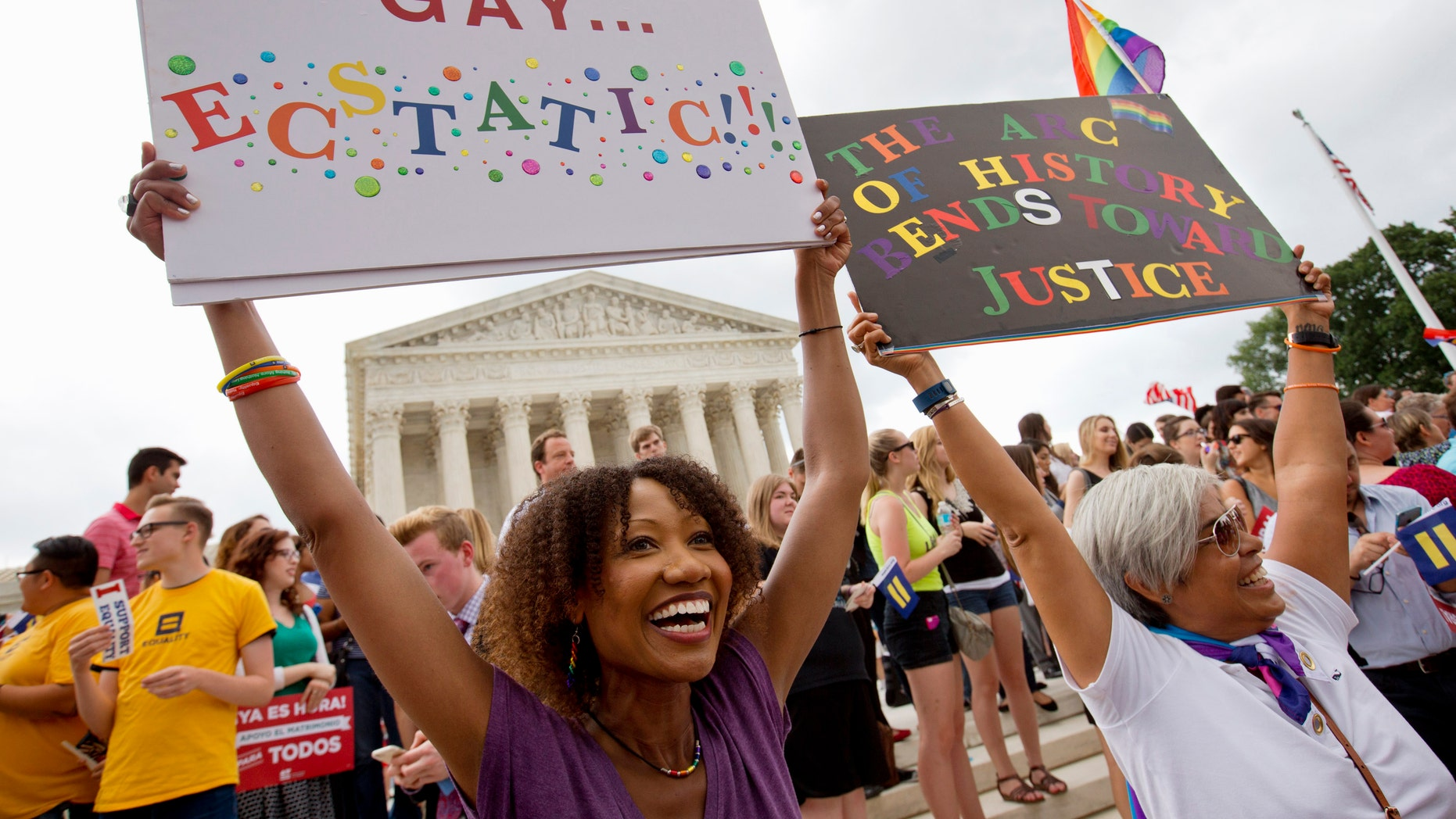 Ikeita Cantu, left, and her wife Carmen Guzman, of McLean, Va., hold up signs as they celebrate outside of the Supreme Court in Washington, Friday June 26, 2015, after the court declared that same-sex couples have a right to marry anywhere in the US. The couple was married in Canada in 2009 when gay marriage was illegal in Virginia. (AP Photo/Jacquelyn Martin)