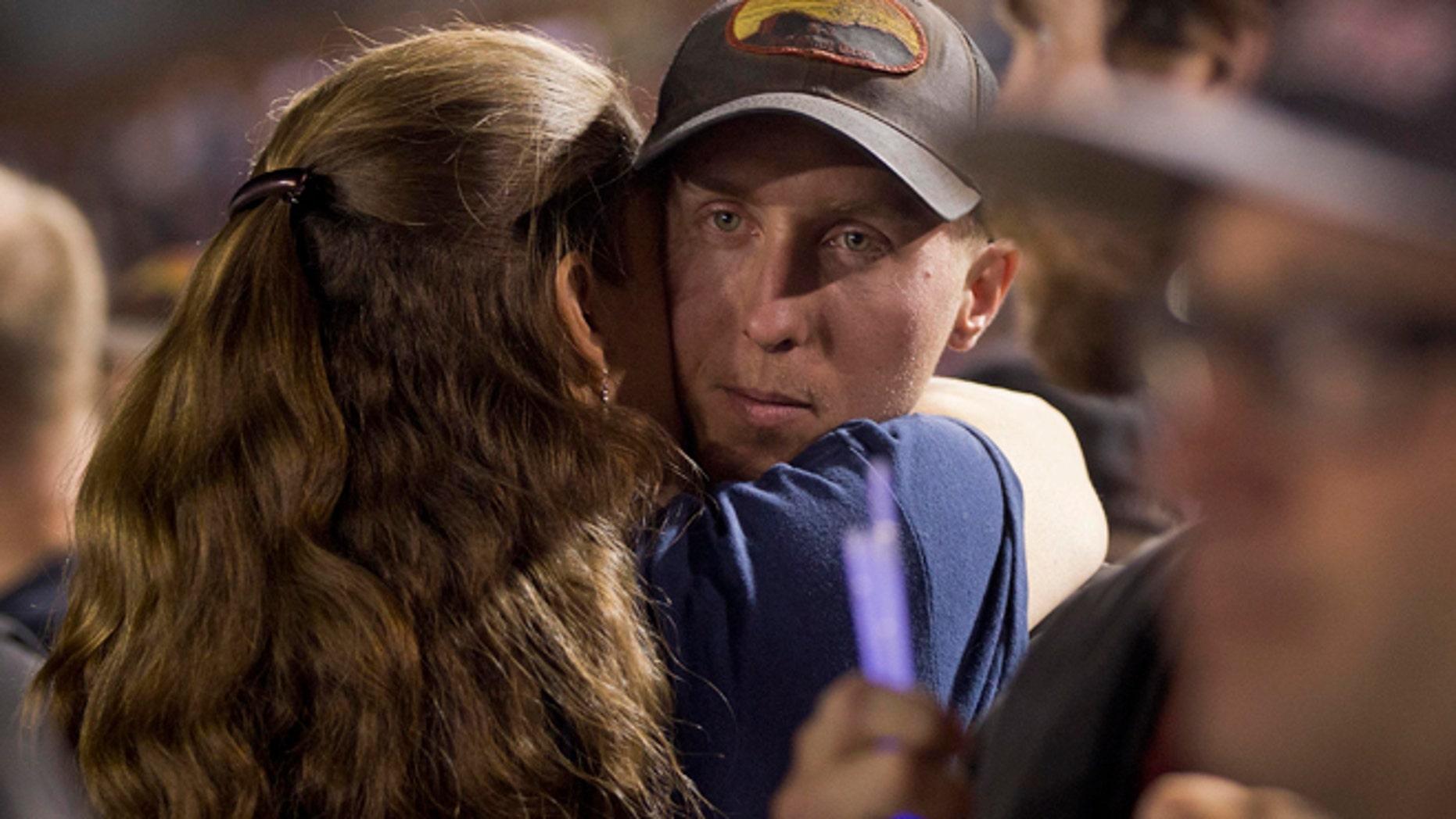 July 2: Firefighter Brendan McDonough embraces a mourner near the end of a candlelight vigil in Prescott, Ariz.