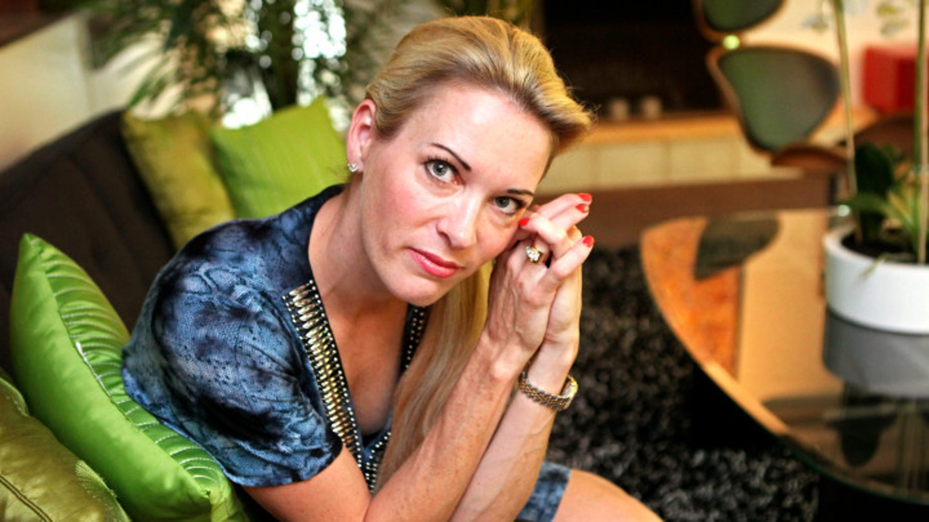 In this photo taken July 17, 2012  Suzy Favor Hamilton poses for a portrait at her home in Shorewood Hills a suburb of Madison, Wis. The three-time Olympian has admitted leading a double life as an escort. She apologized Thursday, Dec. 20, 2012, after a report by The Smoking Gun website said she had been working as a prostitute in Las Vegas. (AP Photo/Milwaukee Journal-Sentinel, Michael Sears)