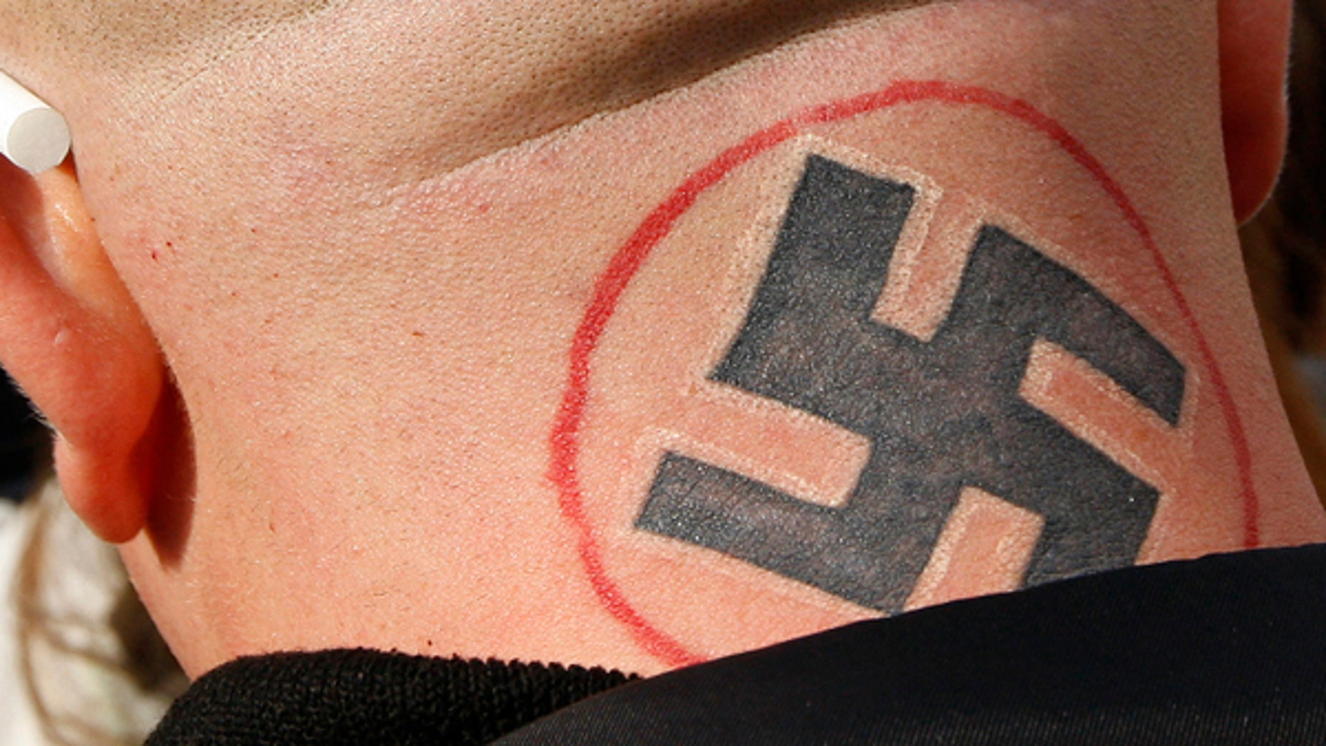 A swastika is seen on a man's neck.