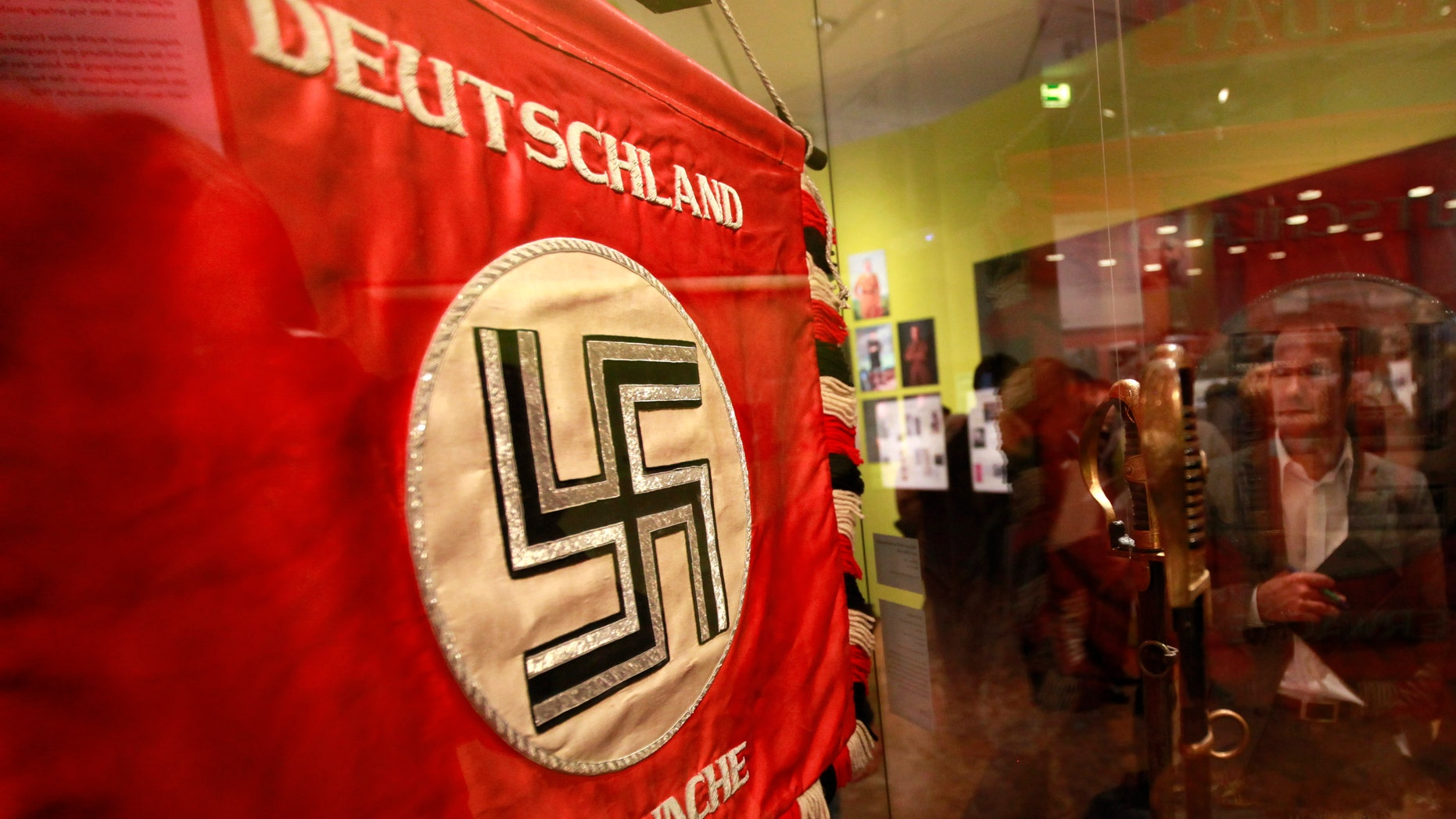 "File photo - A flag with the Nazi swastika is pictured at the media preview of ""Hilter und die Deutsche Volksgemeinschaft und Verbrechen"" (Hitler and the German Nation and Crime) at the Deutsche Historisches Museum (German Historical Museum) in Berlin Oct. 13, 2010. The words on the flag read ""Germany wake up"". (REUTERS/Fabrizio Bensch)"