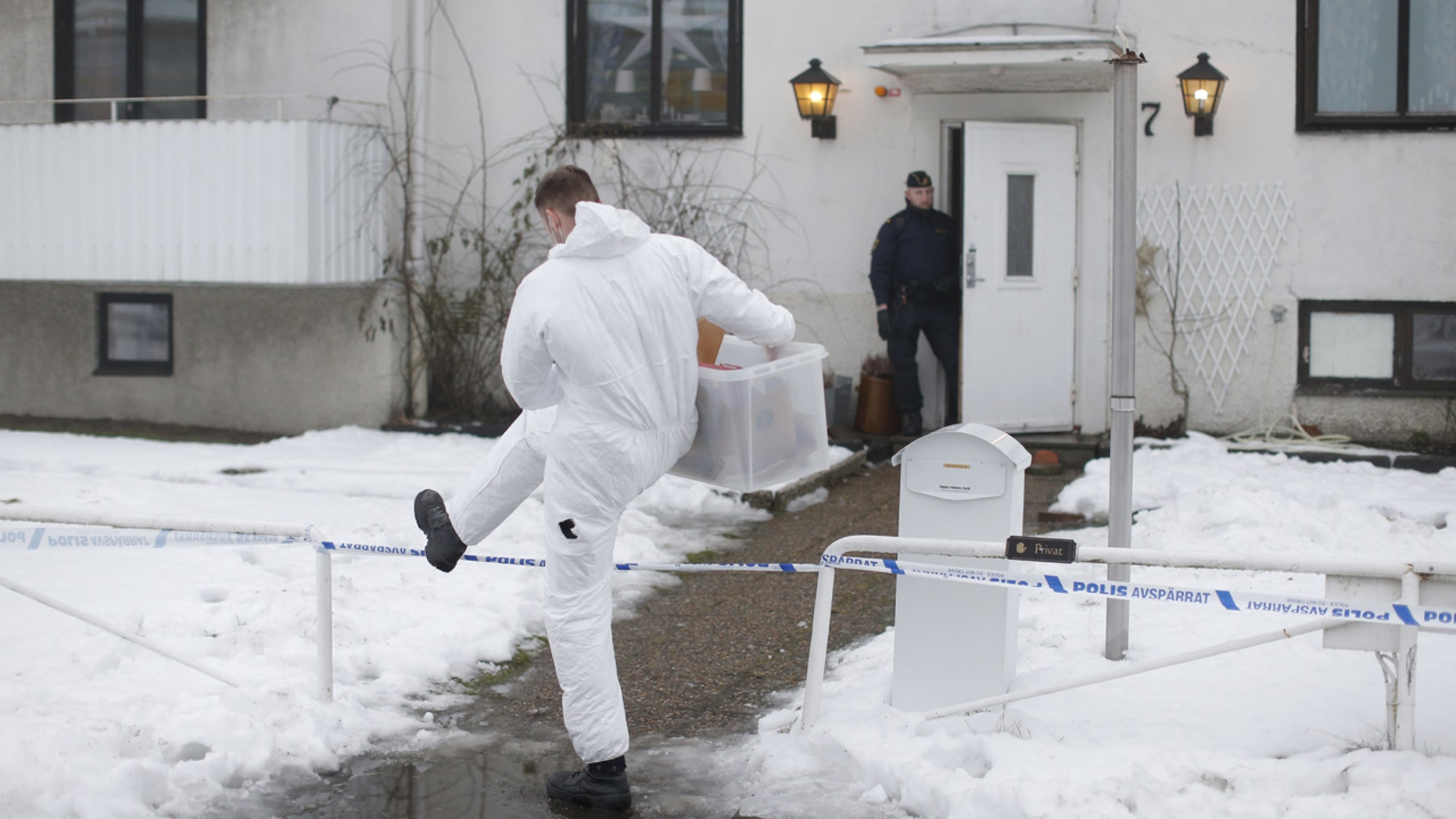 Jan. 25, 2016: A forensic police officer carries a box of evidence following a search in front of a refugee center in Molndal outside Gothenburg, Sweden.