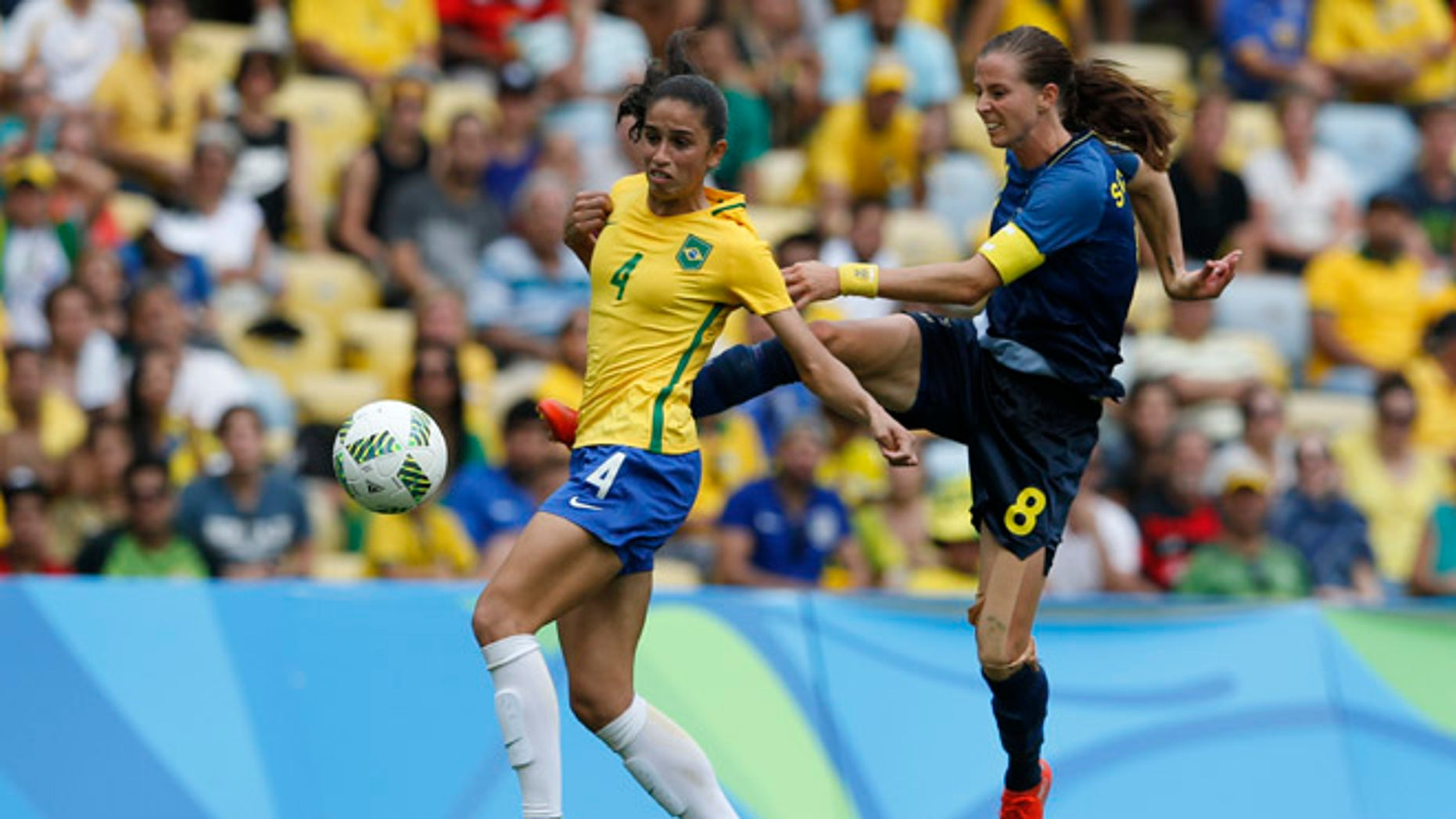 Sweden's Lotta Schelin, right, kicks the ball challenged by Brazil's Rafaelle during a extra time of a semi-final match of the women's Olympic football tournament between Brazil and Sweden at the Maracana stadium in Rio de Janeiro, Brazil, Tuesday Aug. 16, 2016.