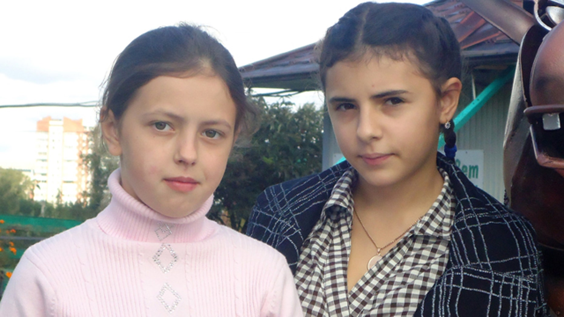 Sept. 11, 2011: 12-year-old Anna, left, and Irina, right, pose in the city of Kopeisk in Russia's Ural Mountains. Two Russian families on Monday won a US$100,000-compensation each from a maternity home that accidentally switched their 12-year old daughters at birth, but they remained at loss about how to fix their shattered lives.