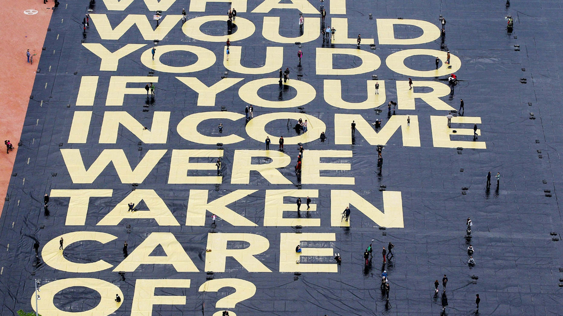 "May 14, 2016: A huge poster reading '""What would you do if your income were taken care of?'"" is pictured on the Plaine de Plainpalais square in Geneva, Switzerland."