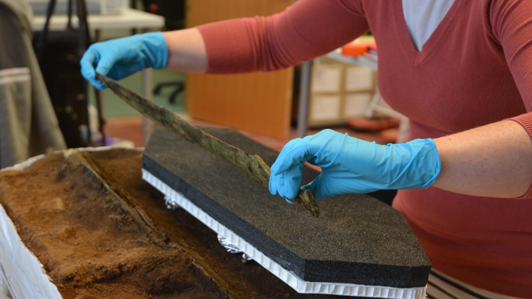 Lifting the Bronze Age sword (© GUARD Archaeology Ltd).