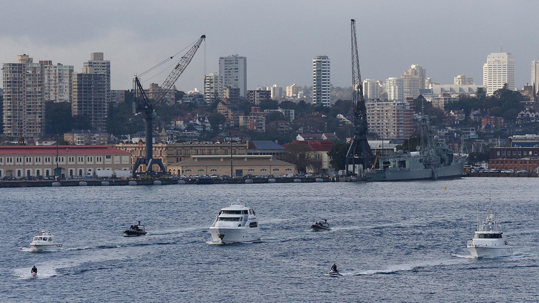 A flotilla including a motor launch crosses Sydney Harbor.