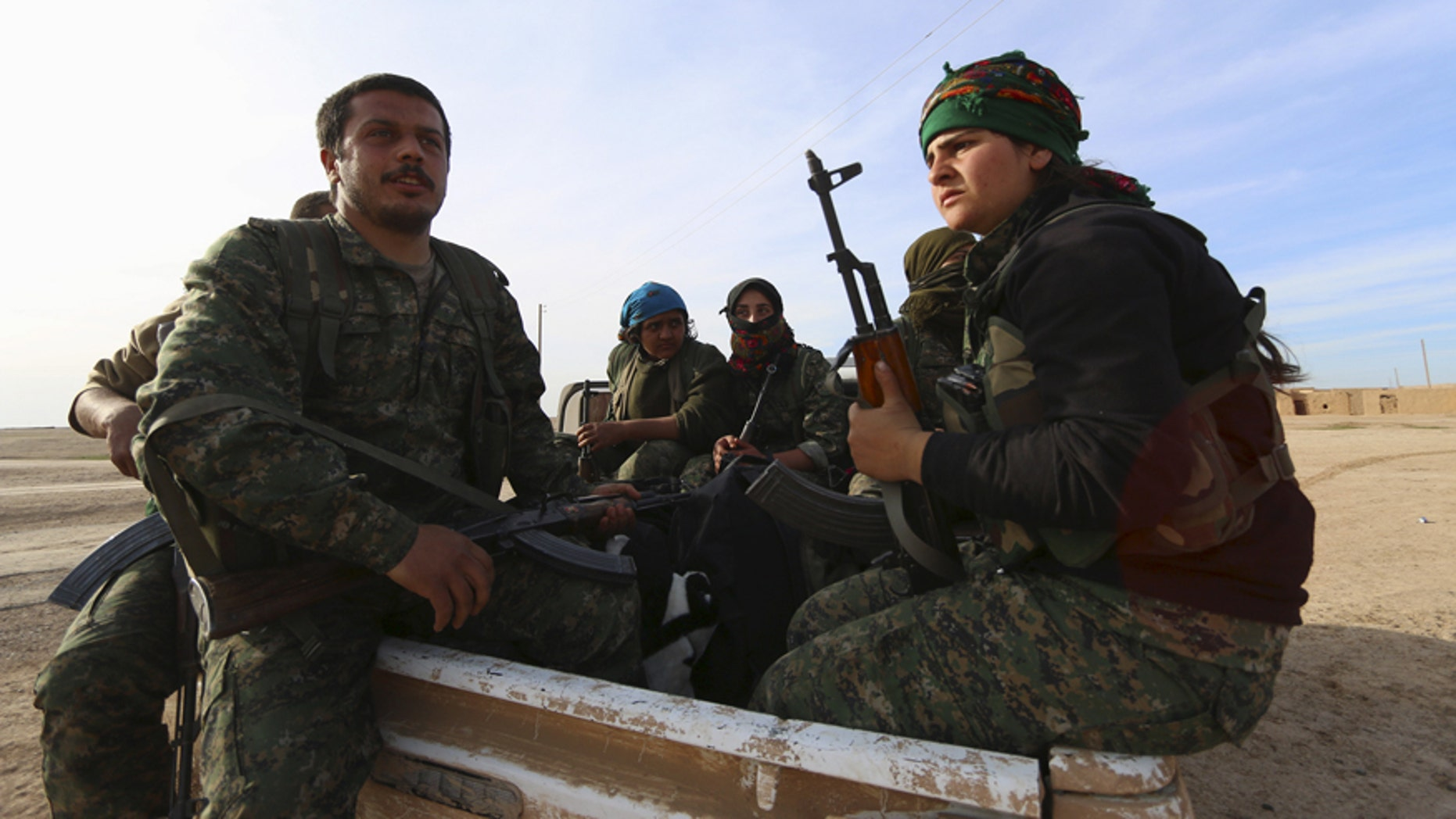Feb. 17, 2016: Fighters from the Democratic Forces of Syria carry their weapons on the back of a pick-up truck in Ghazila village after taking control of the town from Islamic State forces in the southern countryside of Hasaka, Syria.