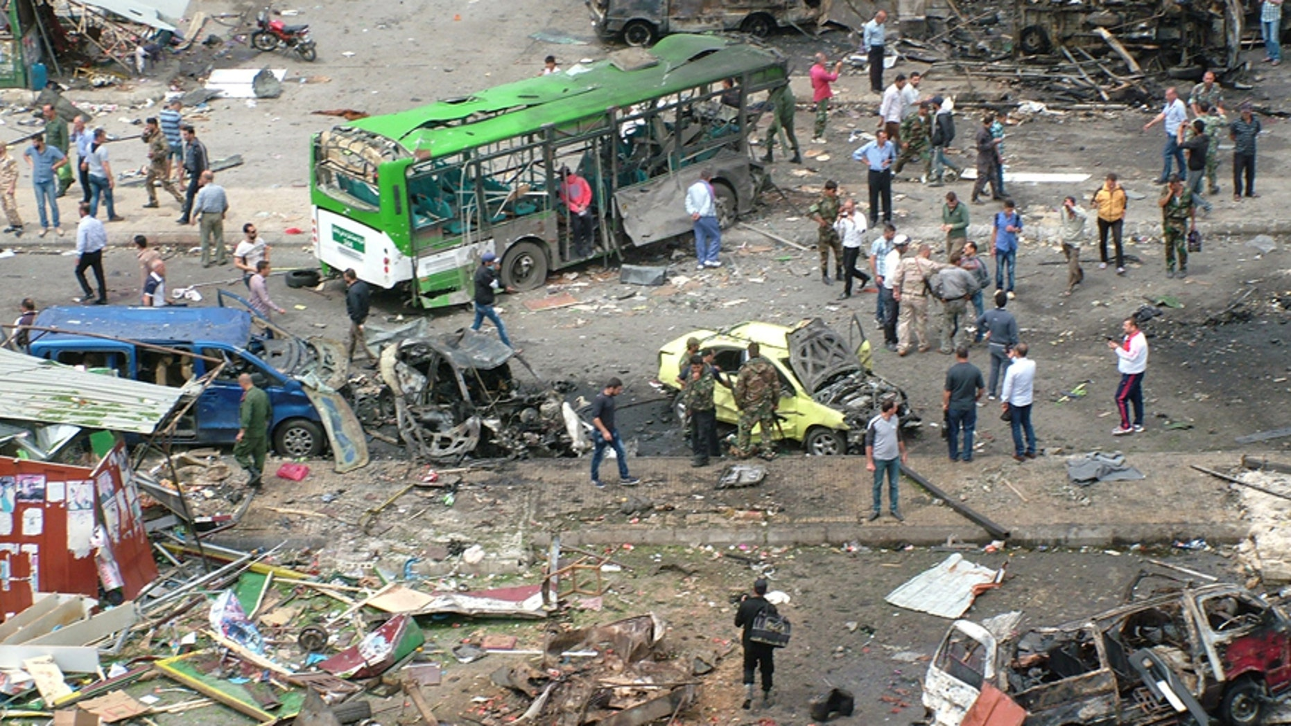May 23, 2016: In this photo released by the Syrian official news agency SANA, Syrians inspect damages after a bombing attack at a bus station, in the coastal town of Tartus, Syria.