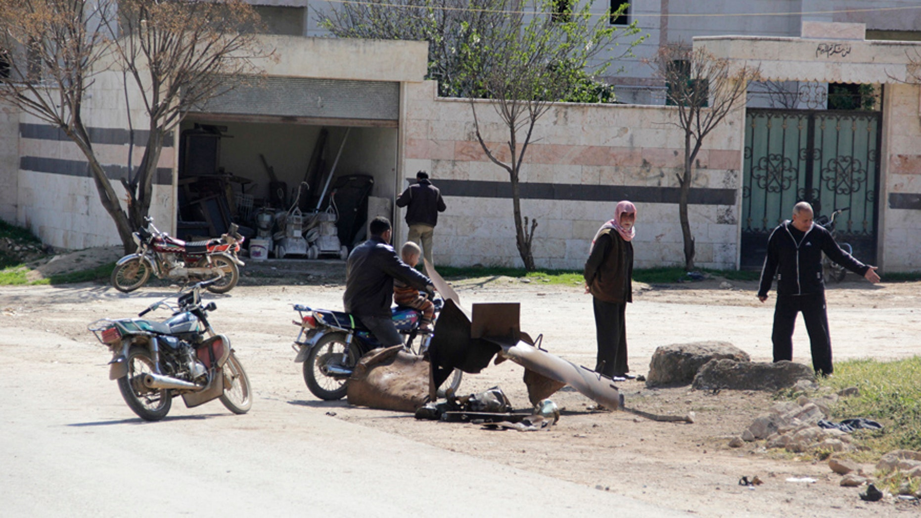 March 17, 2015: People inspect a site targeted by what activists said was a poison gas attack in the village of Sarmin in Idlib province.