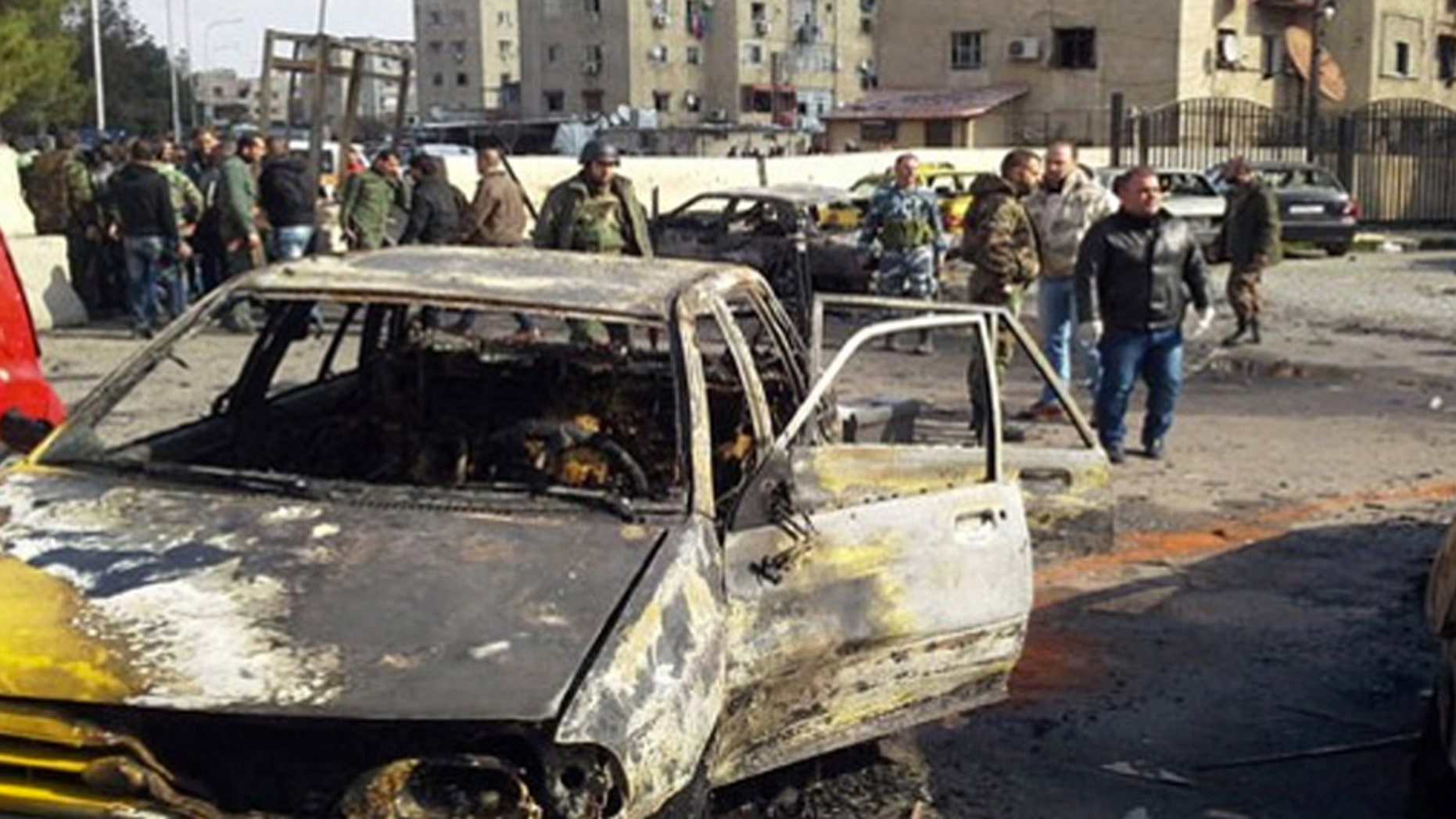 Feb. 9, 2016: In this photo released by the Syrian official news agency SANA, soldiers and plainclothes policemen gather at the scene of an explosion that killed tens of people and wounded others in the Syrian capital of Damascus.
