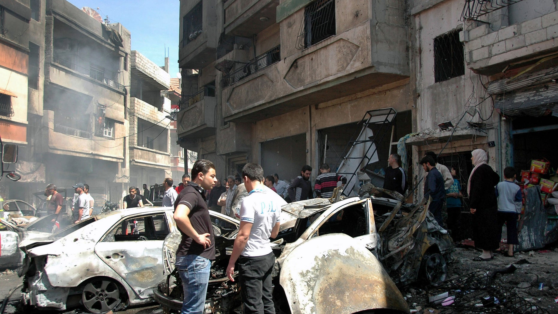 April 29, 2014 - Syrian people gather at the site of one of 2 car bombs that exploded in the pro-government district of Zahra in the central Syrian city of Homs, Syria. Photo provided by Syrian official news agency SANA.
