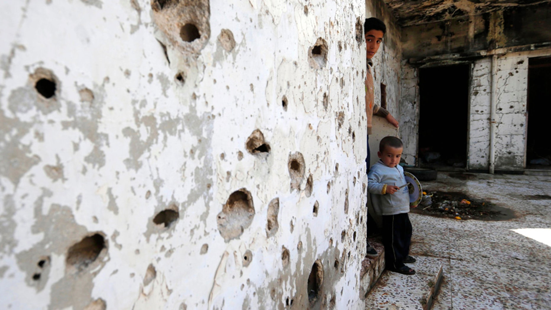 Feb. 26, 2016: Syrian boys are seen inside their destroyed house at neighborhood of Baba Amr in Homs, Syria.