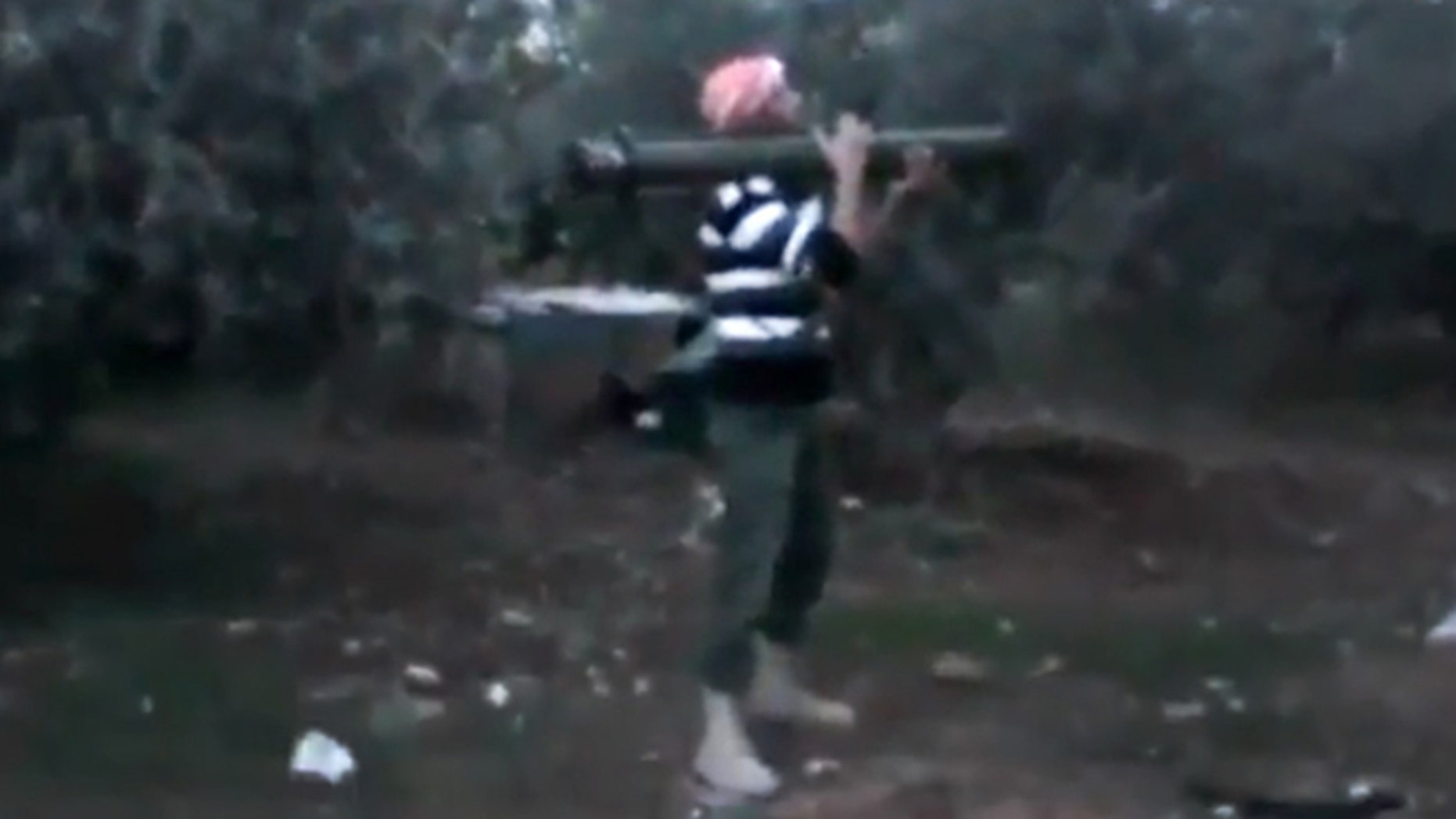 Nov. 27 2012: A Free Syrian Army fighter fires his weapon toward a military tank, unseen, in Daraa, Syria.