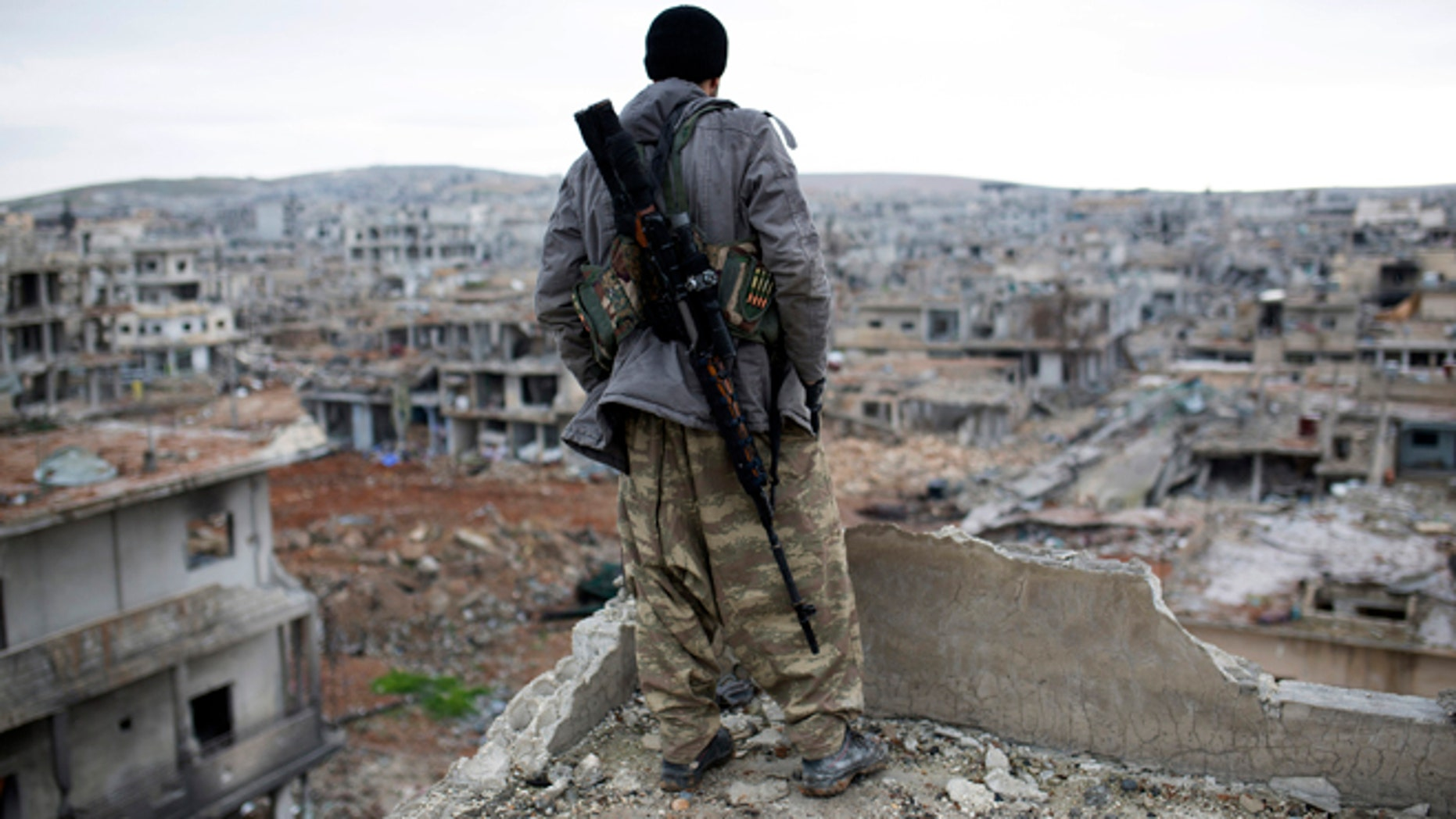 Jan. 30, 2015: In this file photo, a Syrian Kurdish sniper looks at the rubble in the Syrian city of Ain al-Arab, also known as Kobani. Fresh off a major victory in Kobani, Kurdish fighters in Syria have ambitions to become the chief force fighting Islamic State group extremists in the country - building on their victory in Kobani to ally with moderate rebels and push the jihadis ever further.