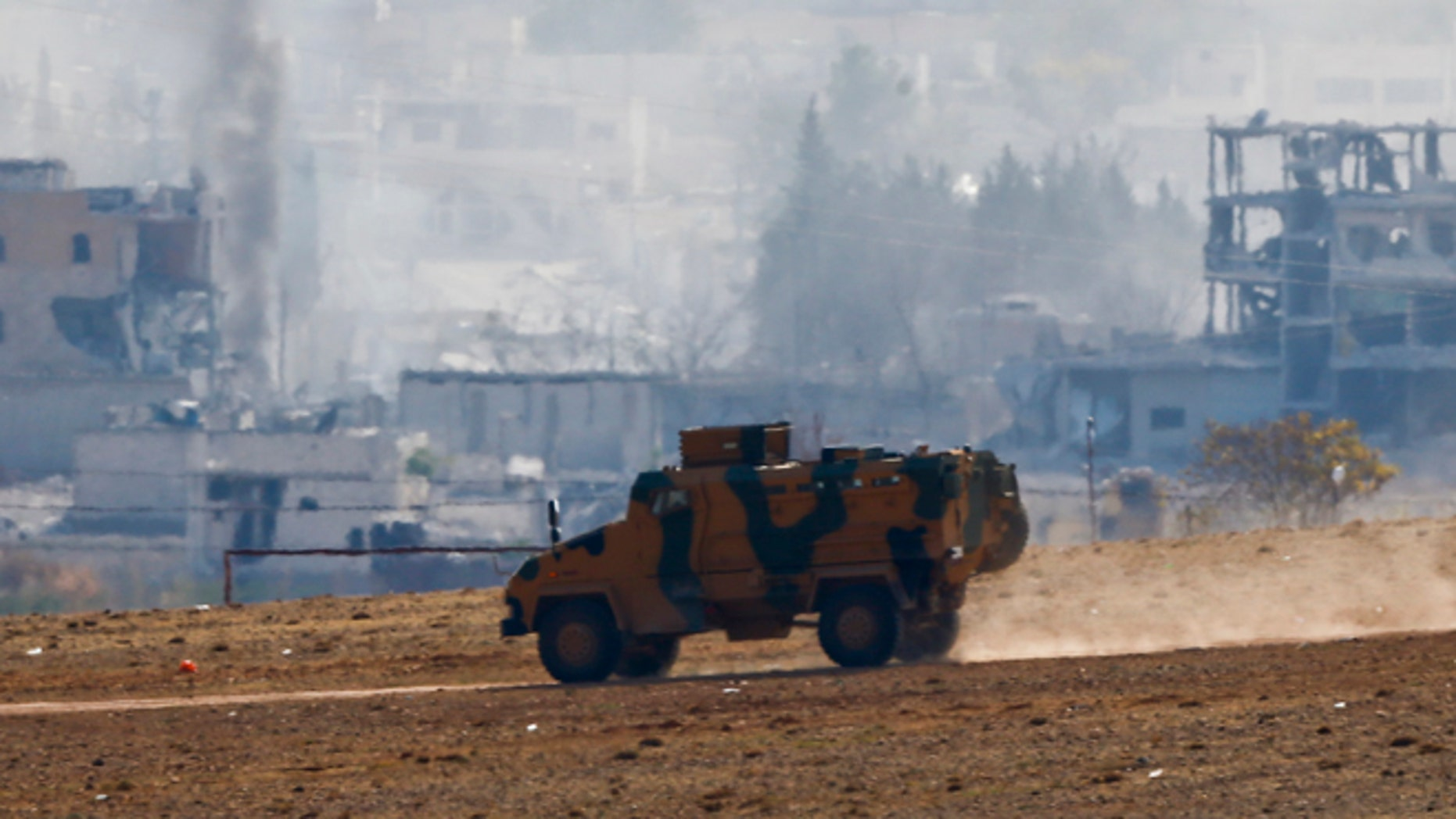 Oct. 29, 2014: Smoke rises from the Syrian town of Kobani as a Turkish army vehicle takes position near the Mursitpinar border crossing on the Turkish-Syrian border in the southeastern town of Suruc in Sanliurfa province.