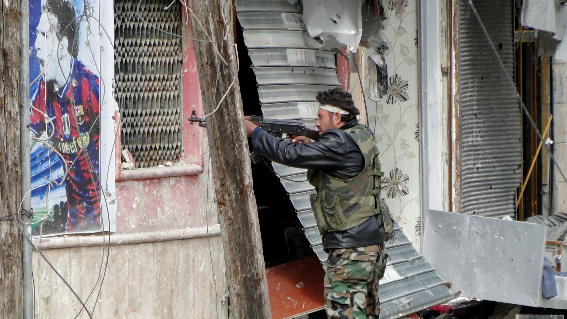 March 28, 2013 - Free Syrian Army fighters take position in Aleppo's Salaheddine district.