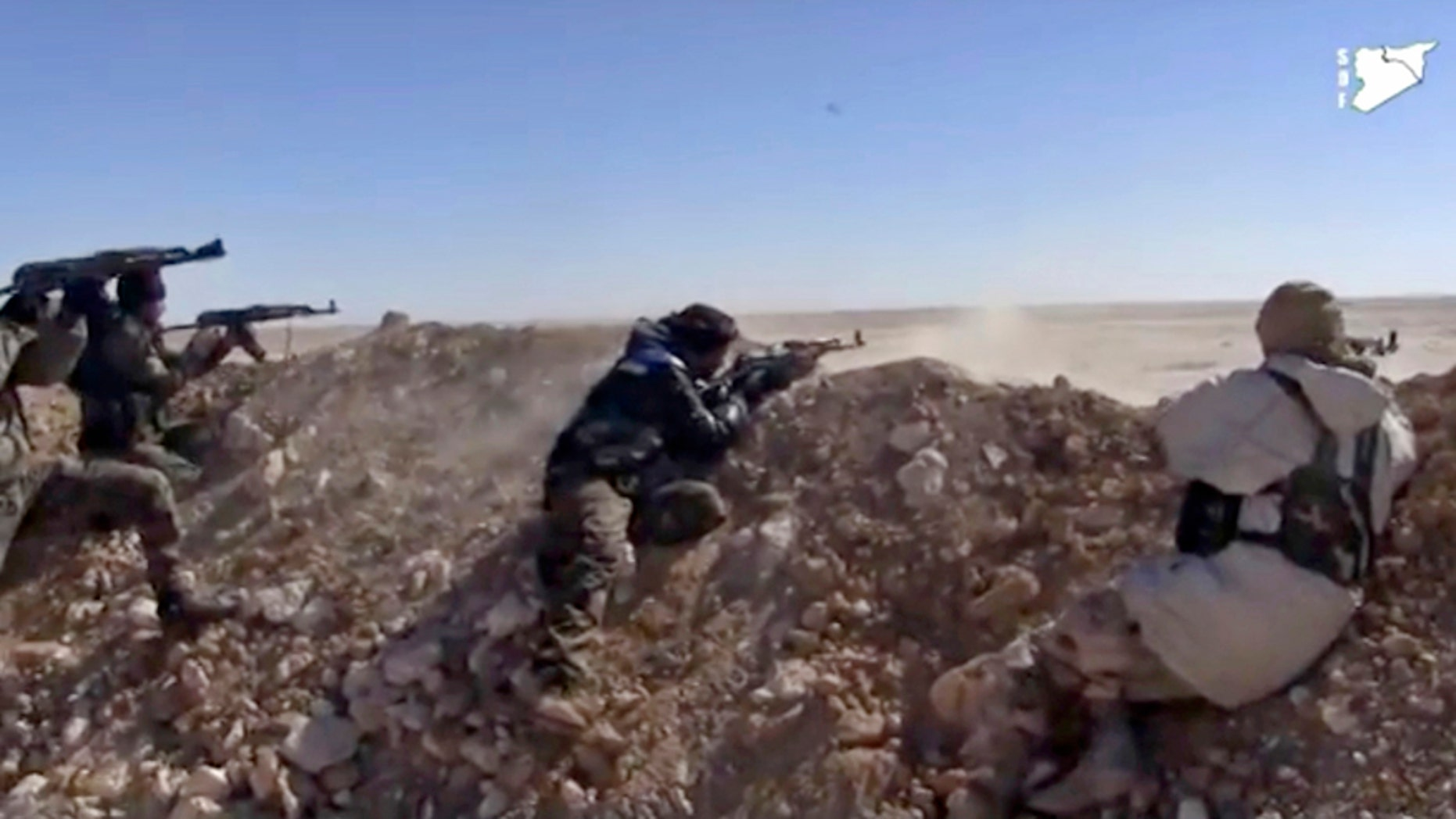 FILE - This frame grab from a  March 6, 2017 video provided by the Syria Democratic Forces (SDF), shows fighters from the SDF opening fire on a position of the Islamic State group in the countryside east of Raqqa, Syria. As the American –backed SDF fighters bear down on Raqqa, the militants have trapped the city's estimated 300,000 residents to use as human shields, ringing the city with land mines to prevent escape. (Syria Democratic Forces, via AP, File)