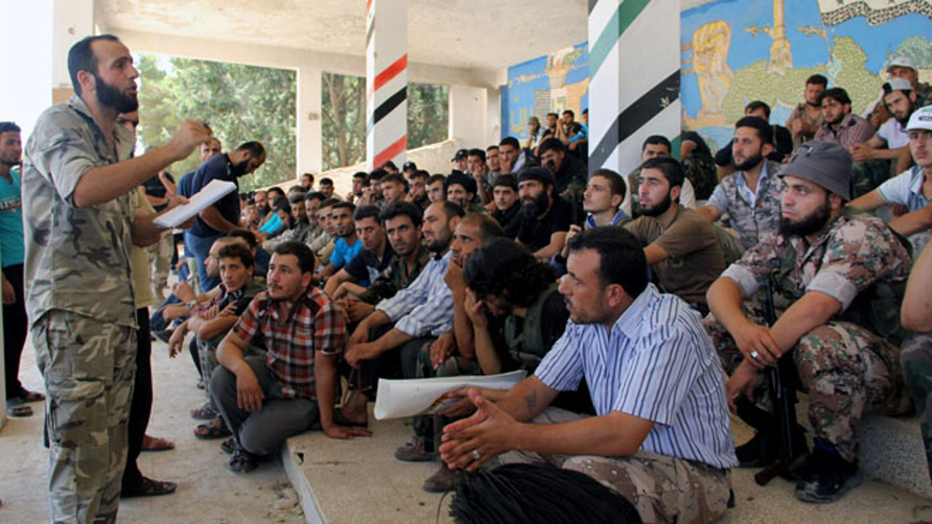 Aug. 13, 2013: In this citizen journalism image provided by Tawhid Brigade, which has been authenticated based on its contents and other AP reporting, Abdul-Qadir Saleh, left, the chief commander of the Tawhid Brigade, the main rebel outfit in Aleppo province, speaks to his fighters ahead of an attack on government troops, in Aleppo, Syria.