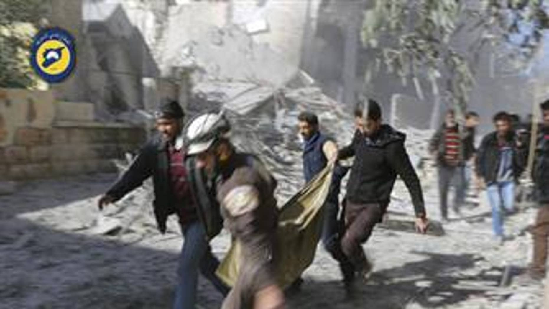 Civil Defense workers and Syrian citizens carry a dead body in the neighborhood of Seif al-Dawleh in Aleppo, Syria, Nov. 19, 2016.