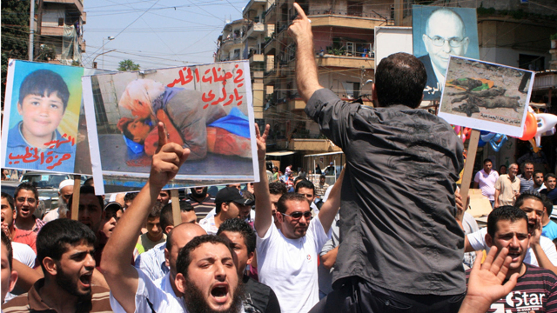 """July 15: Lebanese protesters shout slogans as they carry banners in Arabic that read:"""" you are in heaven my son,"""" center, """"the martyr Hamza el-Khatib,"""" left, and """"Daraa mass graves,"""" right, during a rally in solidarity with Syrian anti-government protesters in the northern city of Tripoli, Lebanon. Syrian security forces fired on protesters in the capital and other major cities Friday, killing at least 14 people as hundreds of thousands gathered for some of the largest anti-government rallies since the uprising began in March, witnesses and activists said."""