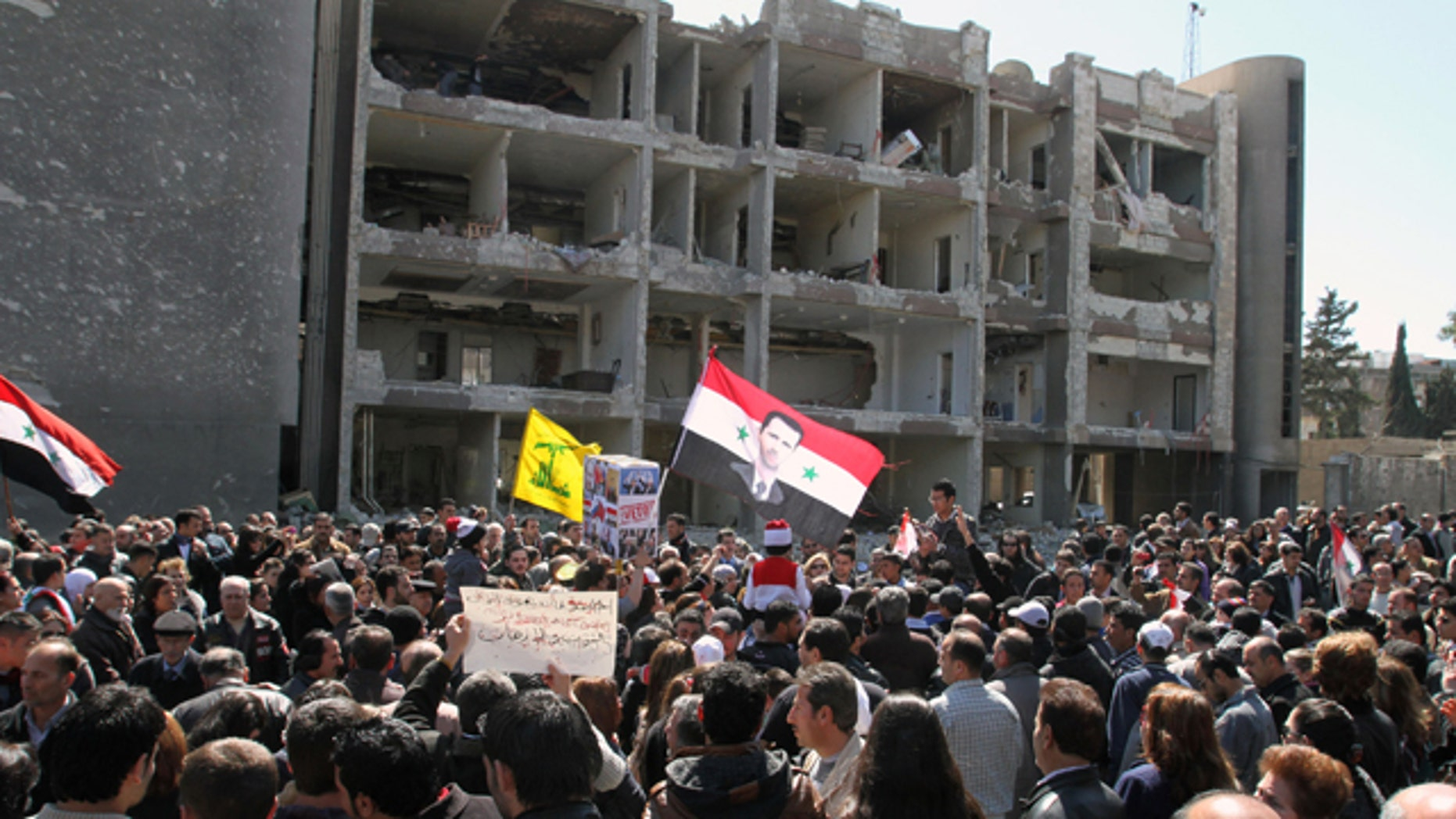 """March 18, 2012: Thousands of people wave Syrian flags, one depicting President Bashar Assad, observe a silent march in front of a damaged government building on al-Qassa street in Damascus, Syria in memory of people who were killed a day earlier by two attacks in the capital Damascus. Three suicide bombings in the capital Damascus on Saturday killed several people. The government blamed those on the opposition, which it claims is made up of """"terrorist"""" groups carrying out a foreign conspiracy."""