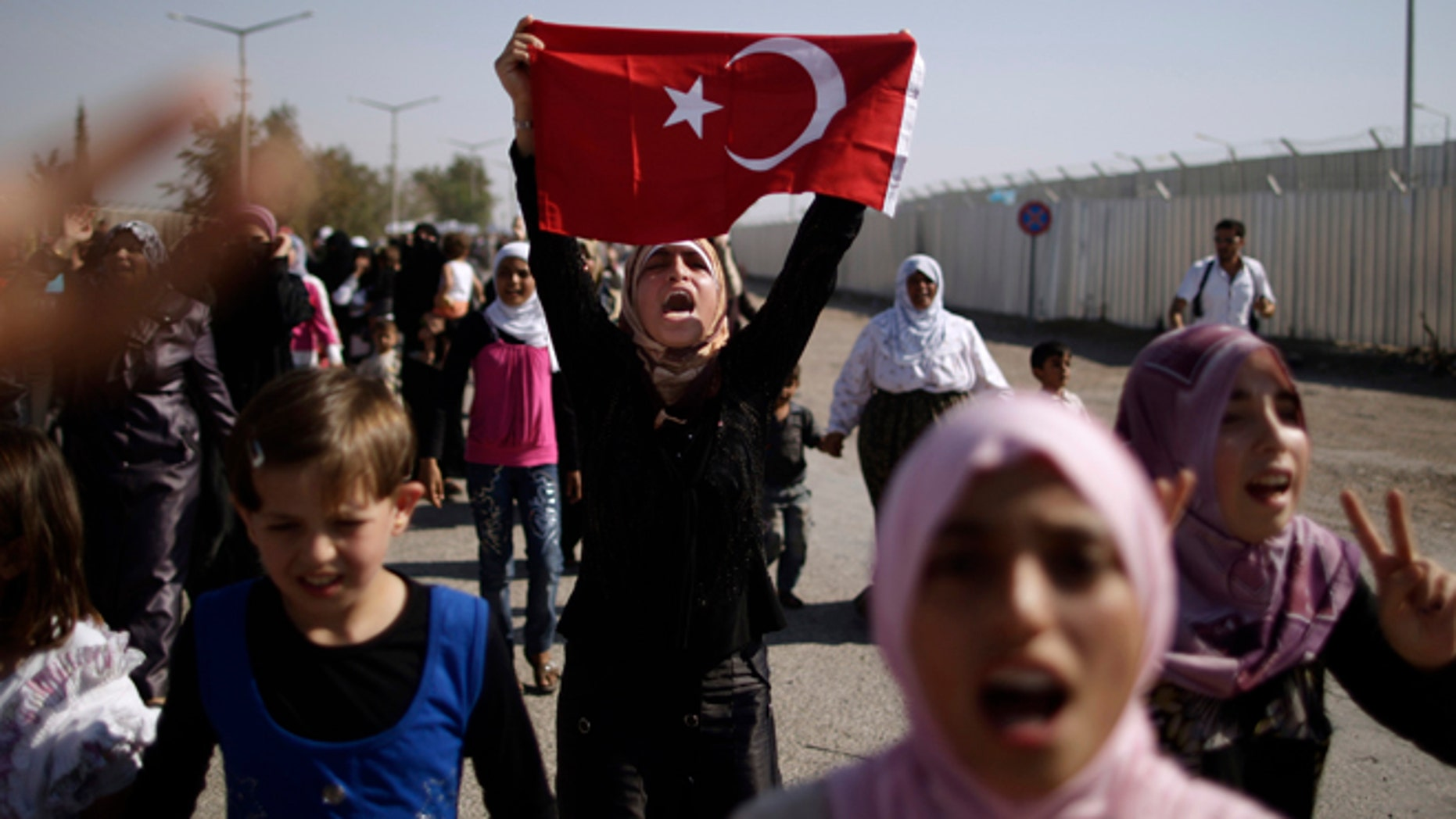 August 28, 2012: Syrians, who fled their homes due to fighting between the Syrian army and the rebels, shout slogans as they march toward the Turkish side of the border, during a protest asking the Turkish government to let them enter to their refugee camps, at the Bab Al-Salameh border crossing, near the Syrian town of Azaz.