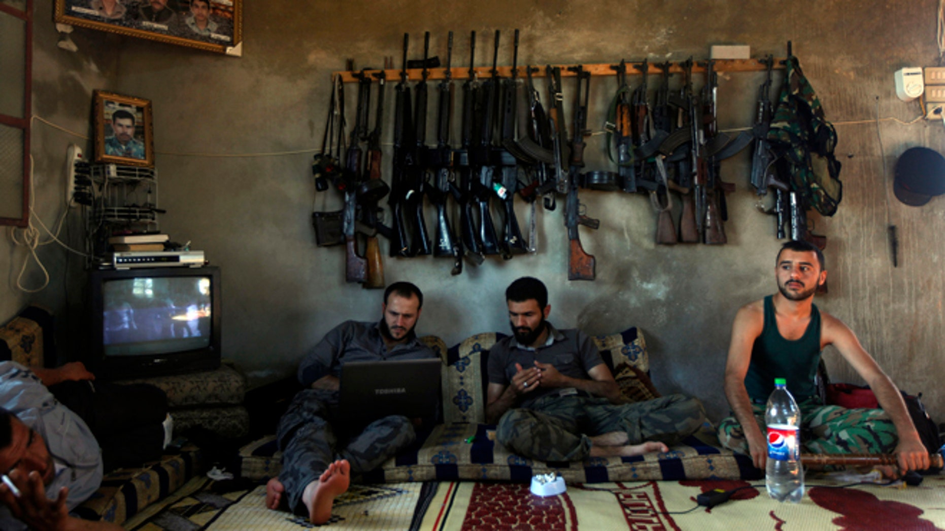 June 12, 2012: Free Syrian Army fighters sit in a house on the outskirts of Aleppo, Syria.