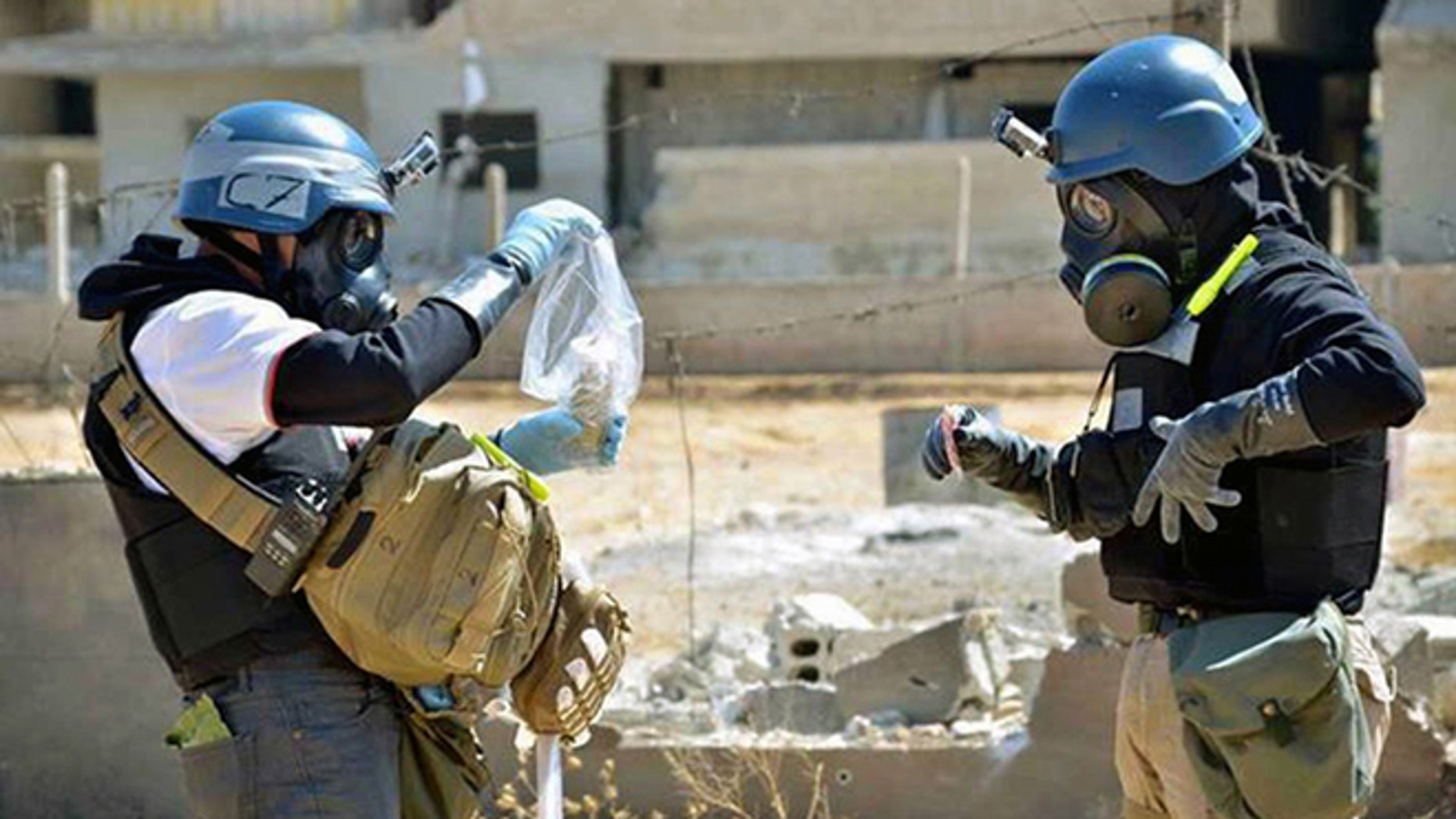 In this Aug. 28, 2013, file photo, a citizen journalism image provided by the United Media Office of Arbeen shows members of the United Nations investigation team take samples from sand near a part of a missile that is likely to be a chemical rocket, according to activists, in the Damascus countryside of Ain Terma, Syria.