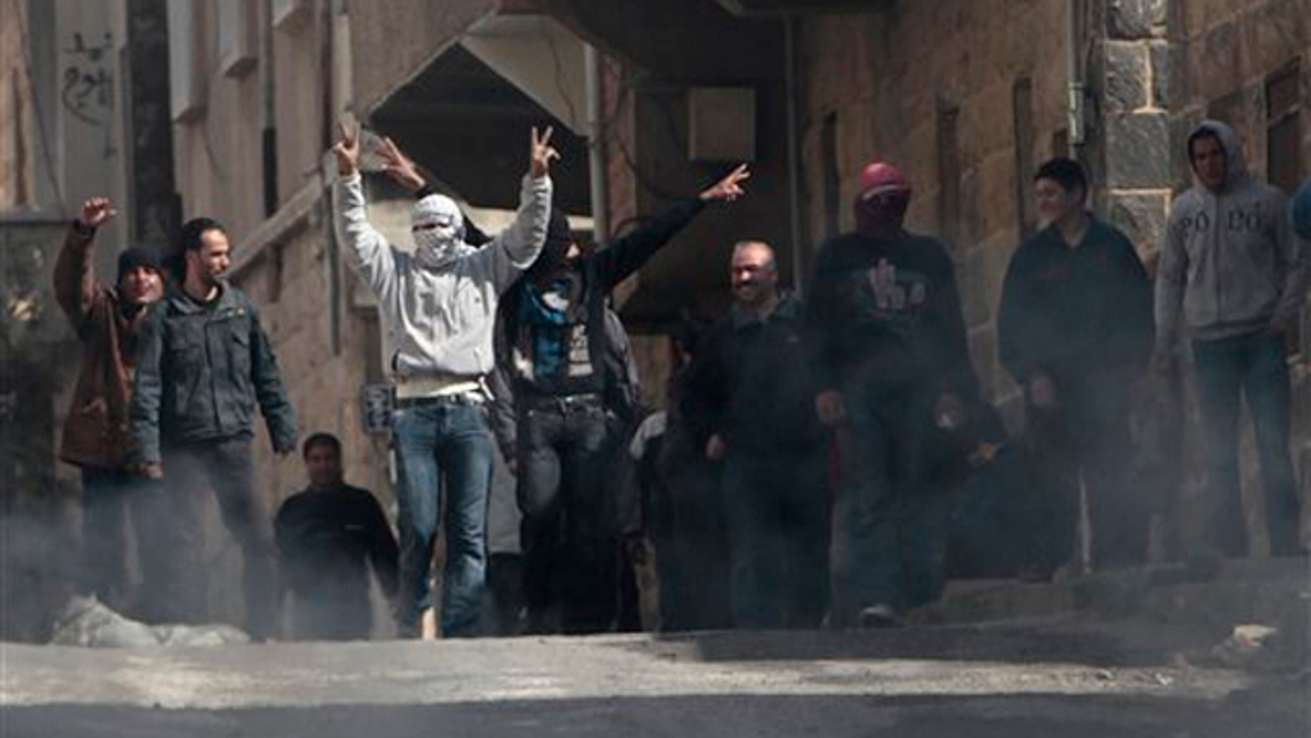 Anti-Syrian government protesters flash V sign as they protest in the southern city of Daraa, Syria, March 23.