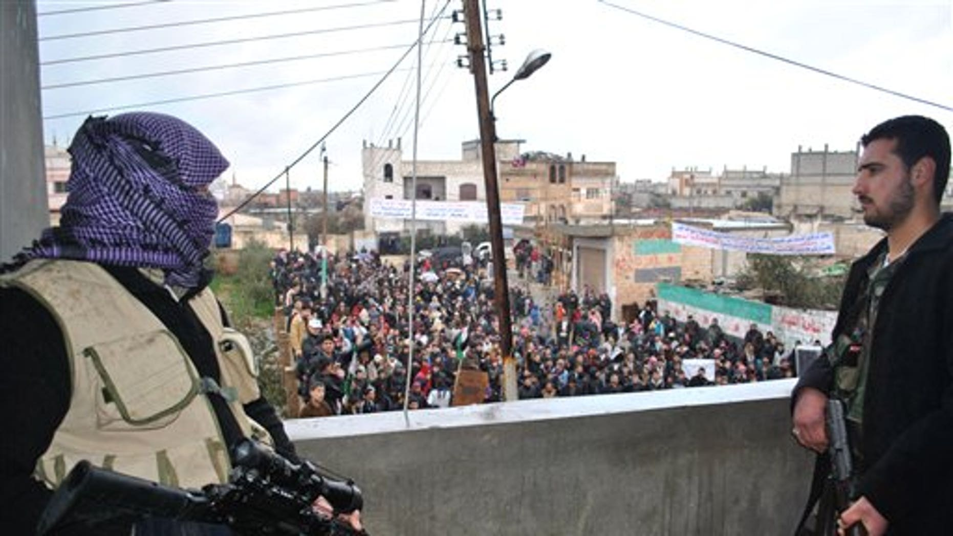 Jan. 27, 2012: Syrian army defectors stand guard on a rooftop to secure an anti-Syrian regime protest in the Deir Baghlaba area in Homs province, central Syria. Armed forces loyal to President Bashar Assad barraged residential buildings with mortars and machine-gun fire, killing at least 30 people, including a family of women and children during a day of sectarian killings and kidnappings in the besieged Syrian city of Homs, activists said Friday.