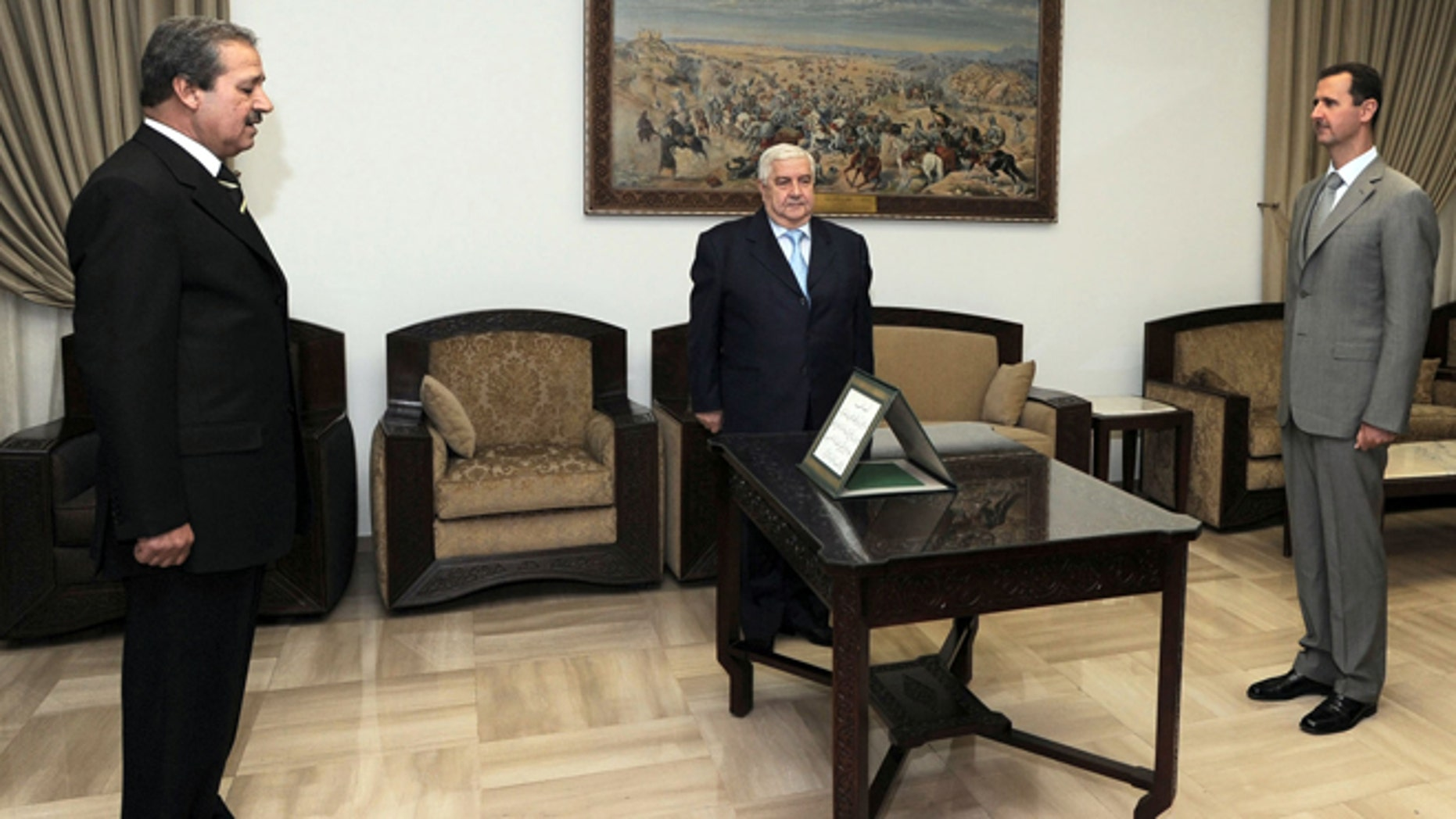 FILE - In this Sept. 16, 2008 file photo provided by the Syrian official news agency SANA, Nawaf  Fares, left, is sworn in as Syria's first ambassador to Iraq in 26 years before Syrian President Bashar Assad, right, and Syrian Foreign Minister Walid Moallem in Damascus.