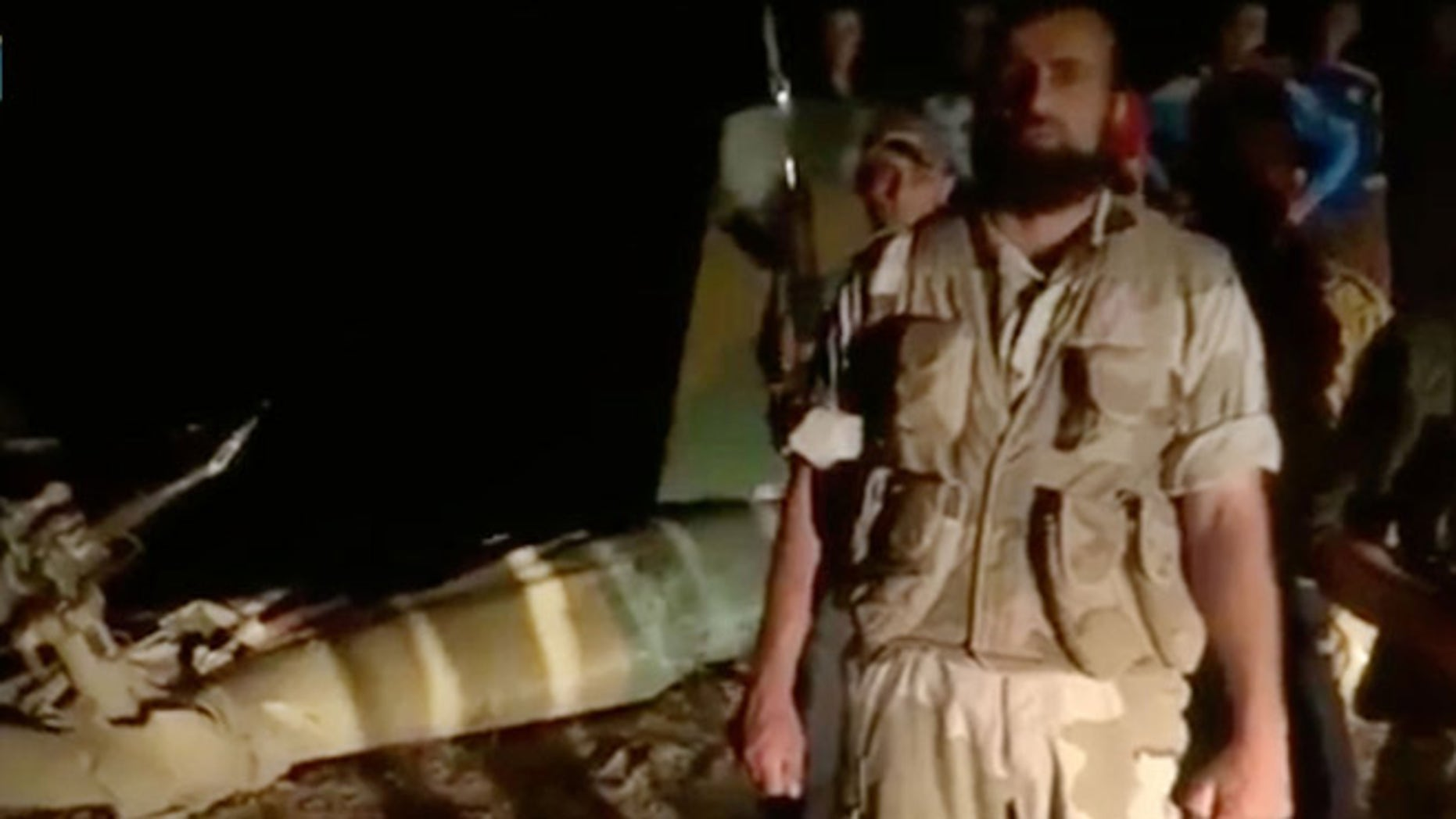 May 5, 2013: In this image taken from video obtained from the Shaam News Network, which has been authenticated based on its contents and other AP reporting, armed men stand near the wreckage of a military helicopter, left, in Deir el-Zour, Syria. Syrian rebels shot down a military helicopter in the country's east, killing eight government troops on board a day after opposition forces entered a sprawling military air base in the north, activists said Monday.