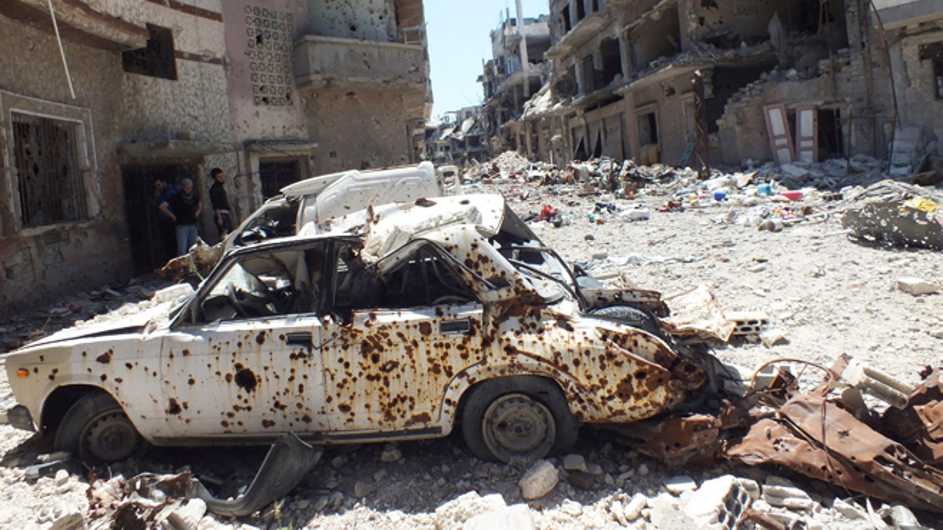 April 28, 2013: A destroyed car is seen on a street lined with buildings damaged by what activists said was shelling by forces loyal to Syria's President Bashar al-Assad in the besieged area of Homs.