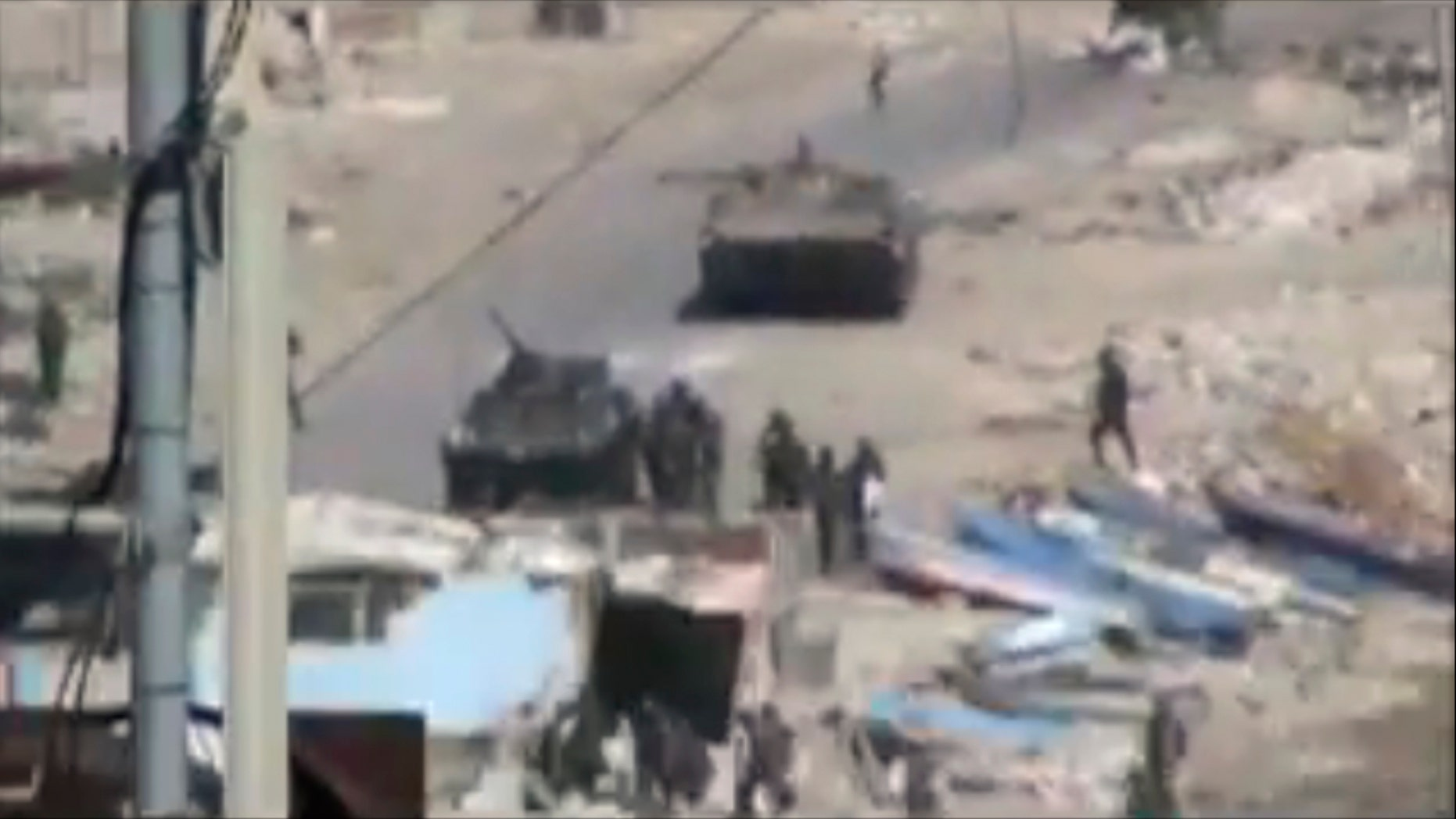 Aug. 17: This image taken from amateur video made available Tuesday purports to show armored vehicles and troops in  Latakia, Syria on Monday. Activists say 15 people died in shootings across Syria Monday including at least five in the coastal city of Latakia where military operations where in their fourth day.
