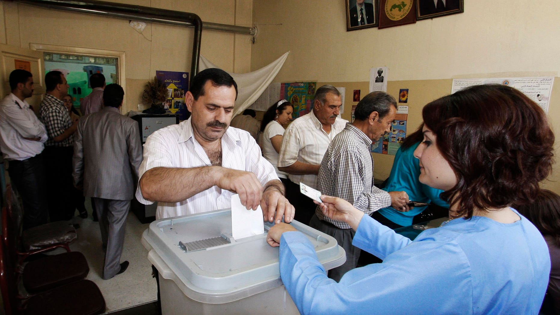 May 7, 2012: In this photo taken during a government-organized tour, a Syrian man casts his vote at a polling station during the parliamentary elections, in Damascus, Syria.