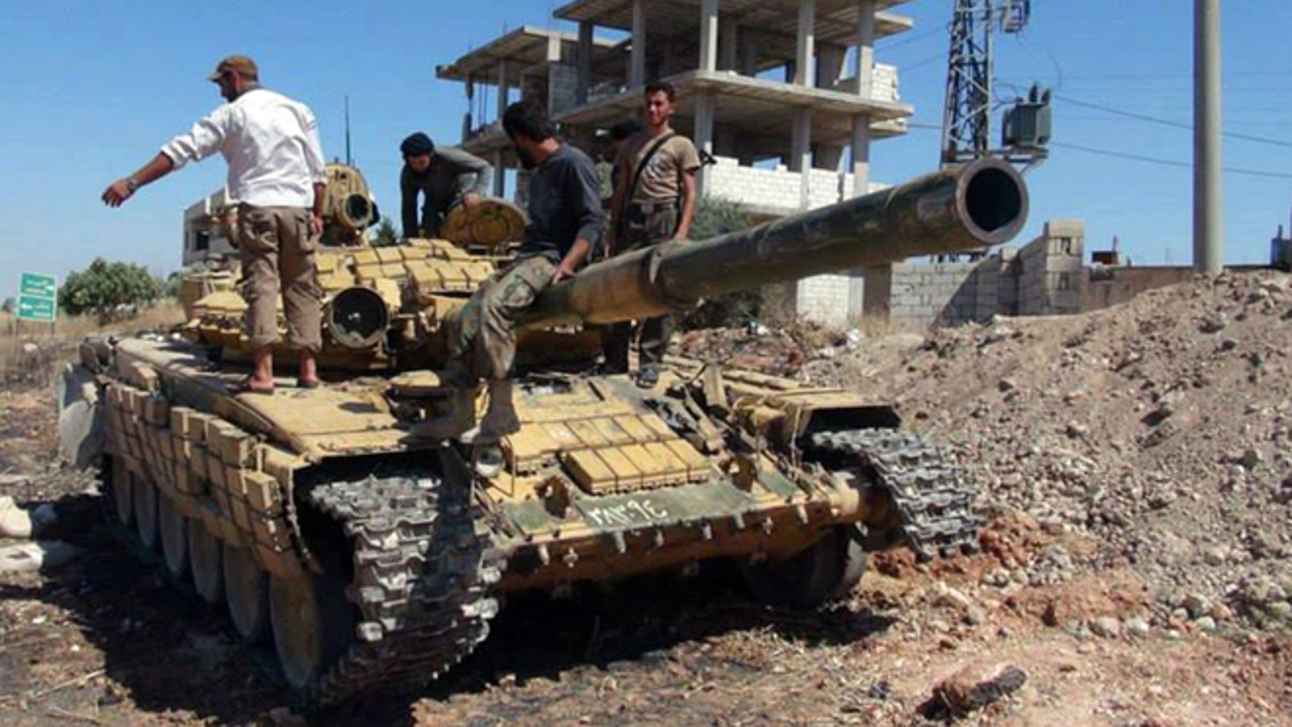 June 14, 2013: In this citizen journalism image provided by Edlib News Network, ENN, Syrian rebels stand on top of a tank they took after storming the Iskan military base in Idlib province, northern Syria. After weeks of fighting the rebels captured tanks as well as other vehicles and artillery in the area.