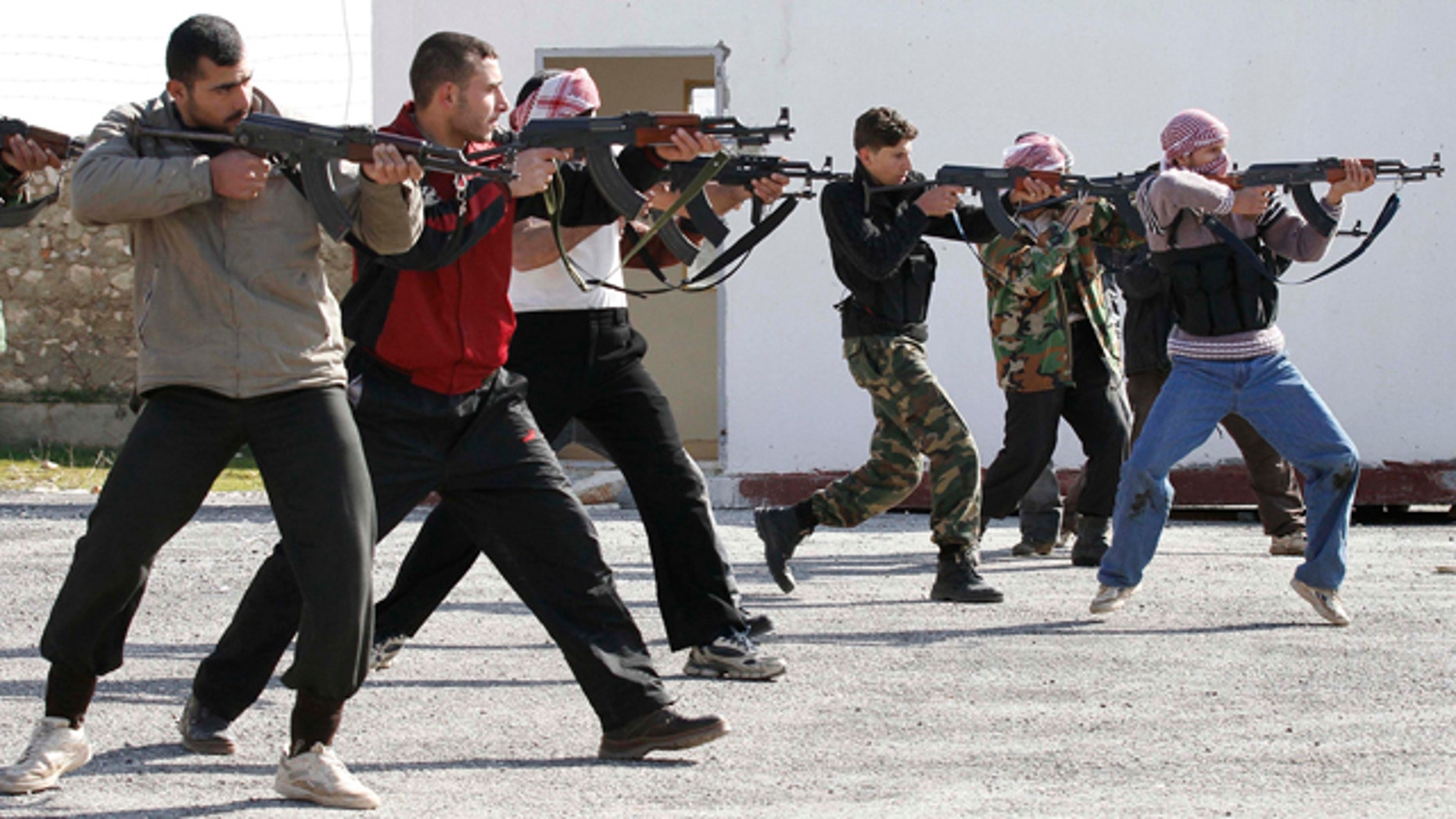 Feb. 14, 2012: FILE- In this file photo, Syrian rebels aim during a weapons training exercise outside Idlib, Syria.
