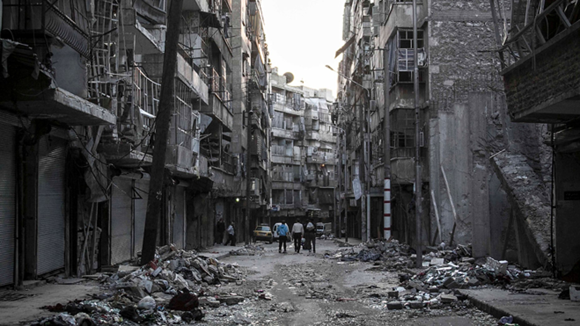 Oct. 27, 2012: In this photo, Syrian residents walk on a street among the debris of buildings damaged by heavy shelling in the southeast of Aleppo City.