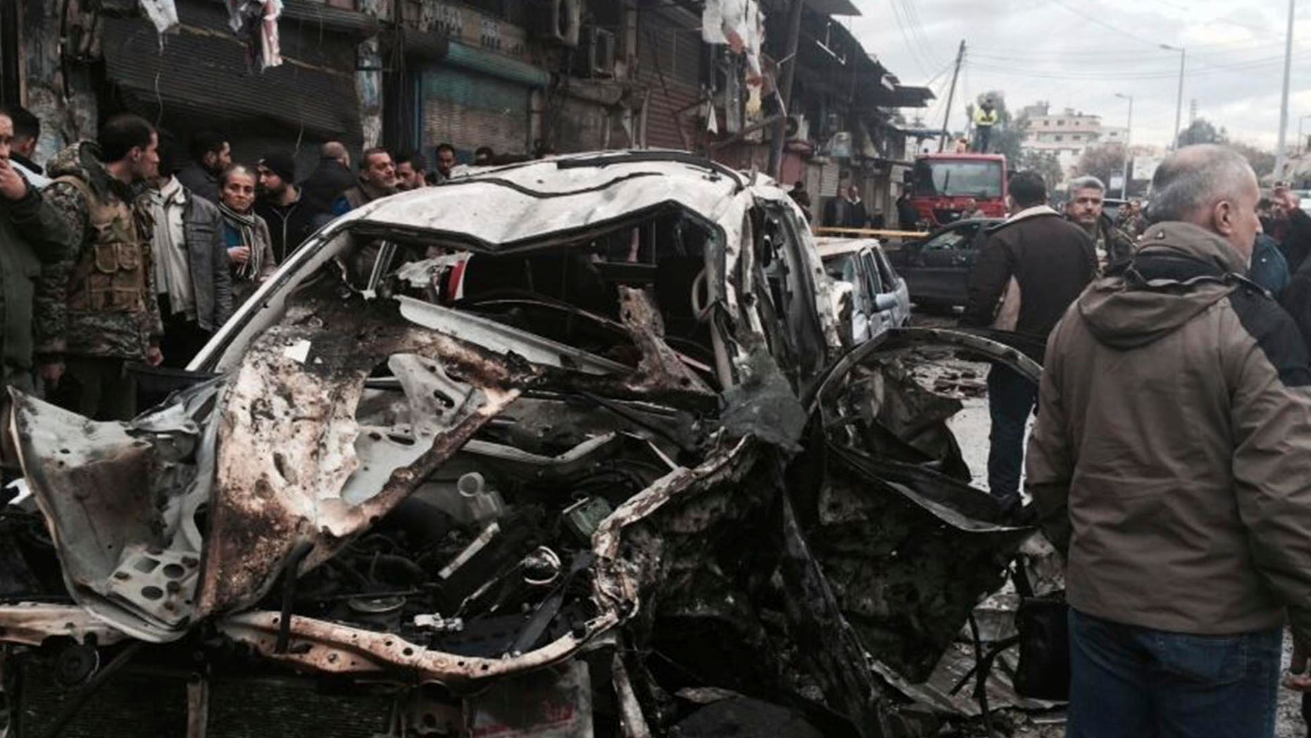 In this photo released by the Syrian official news agency SANA, Syrian citizens gather next to damaged cars at the scene where explosion hit a commercial street, in the costal town of Jableh, Syria, Thursday, Jan. 5, 2017. A large explosion hit a Syrian government-held coastal town on Thursday, killing and wounding several people, according to Syria's state TV an attack that undermined a nearly week-old and already shaky Russia- and Turkey-brokered cease-fire. (SANA via AP)