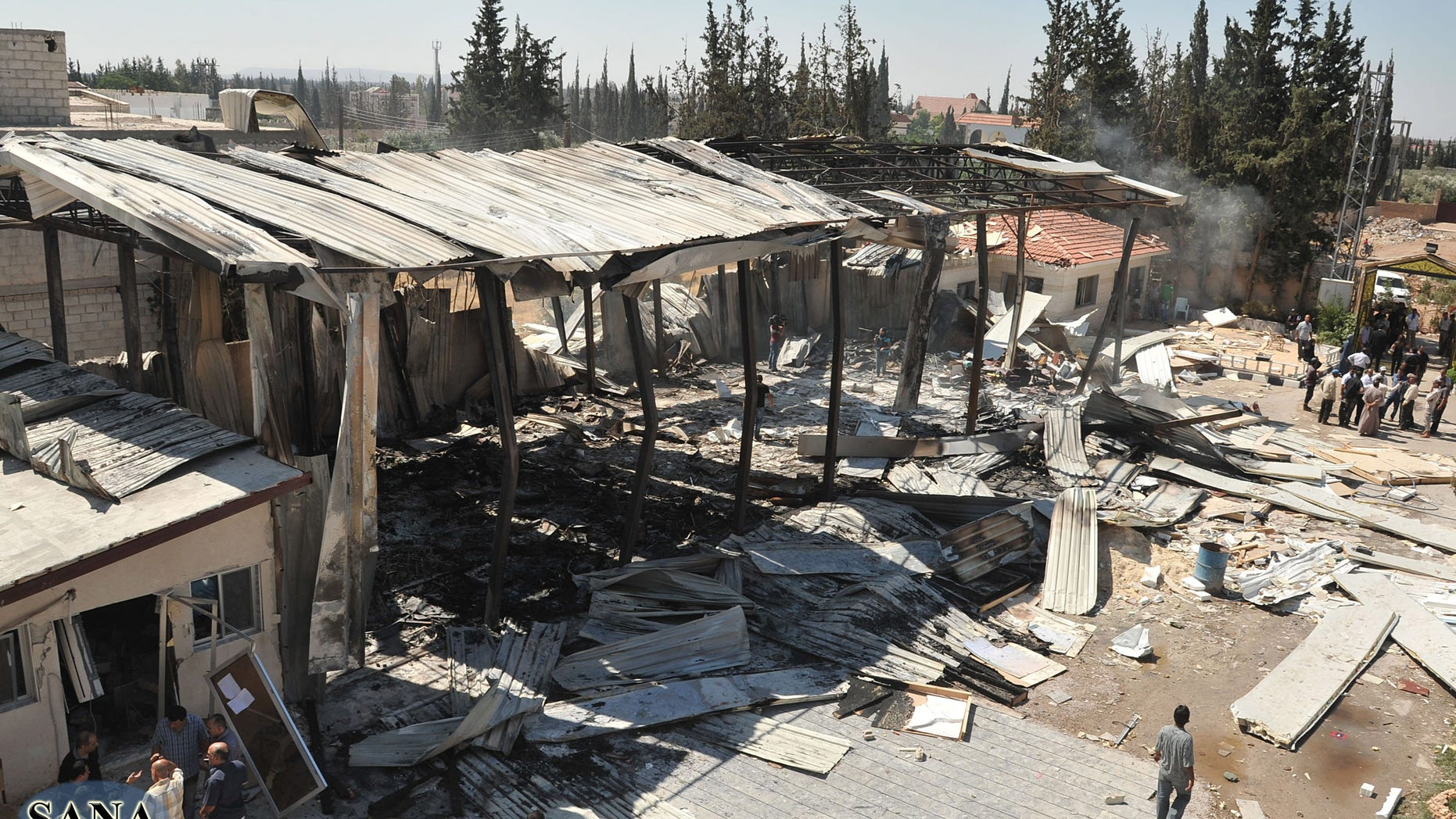 June 27, 2012: In this photo released by the Syrian official news agency, SANA, the damaged Ikhbariya TV compound is seen after it was attacked by gunmen, in in the town of Drousha, about 14 miles south of Damascus, Syria.